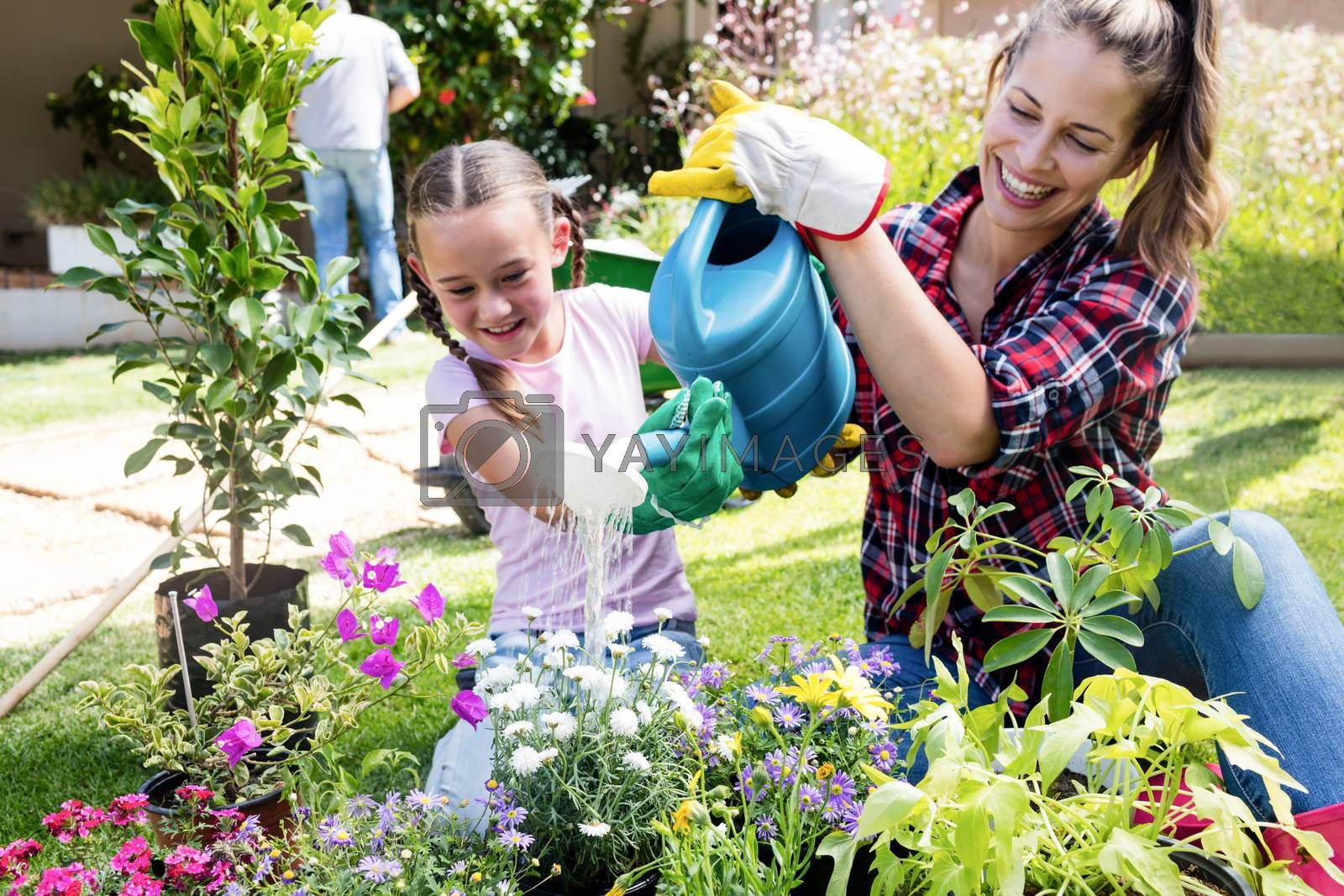 Mother and daughter watering the plants in the garden on a sunny day