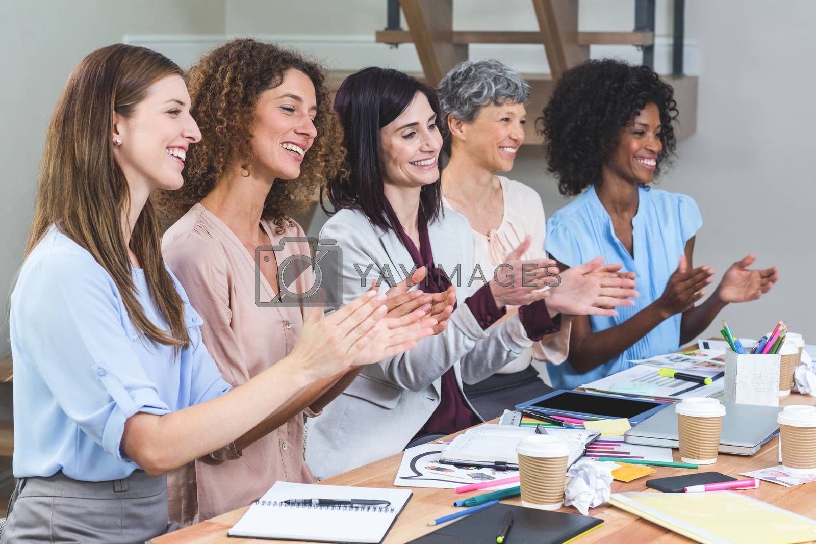 Royalty free image of Group of interior designers applauding in office by Wavebreakmedia