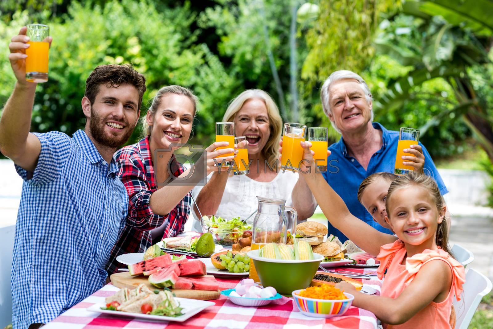 Happy family having breakfast at table in yard