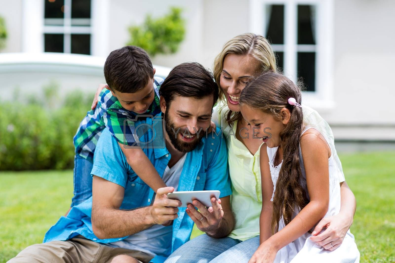 Happy family looking into mobile phone while sitting at yard