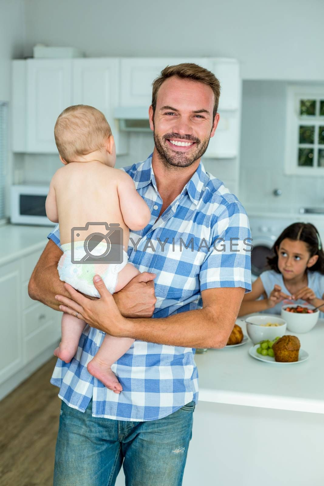 Portrait of happy father carrying son with daughter having breakfast in background