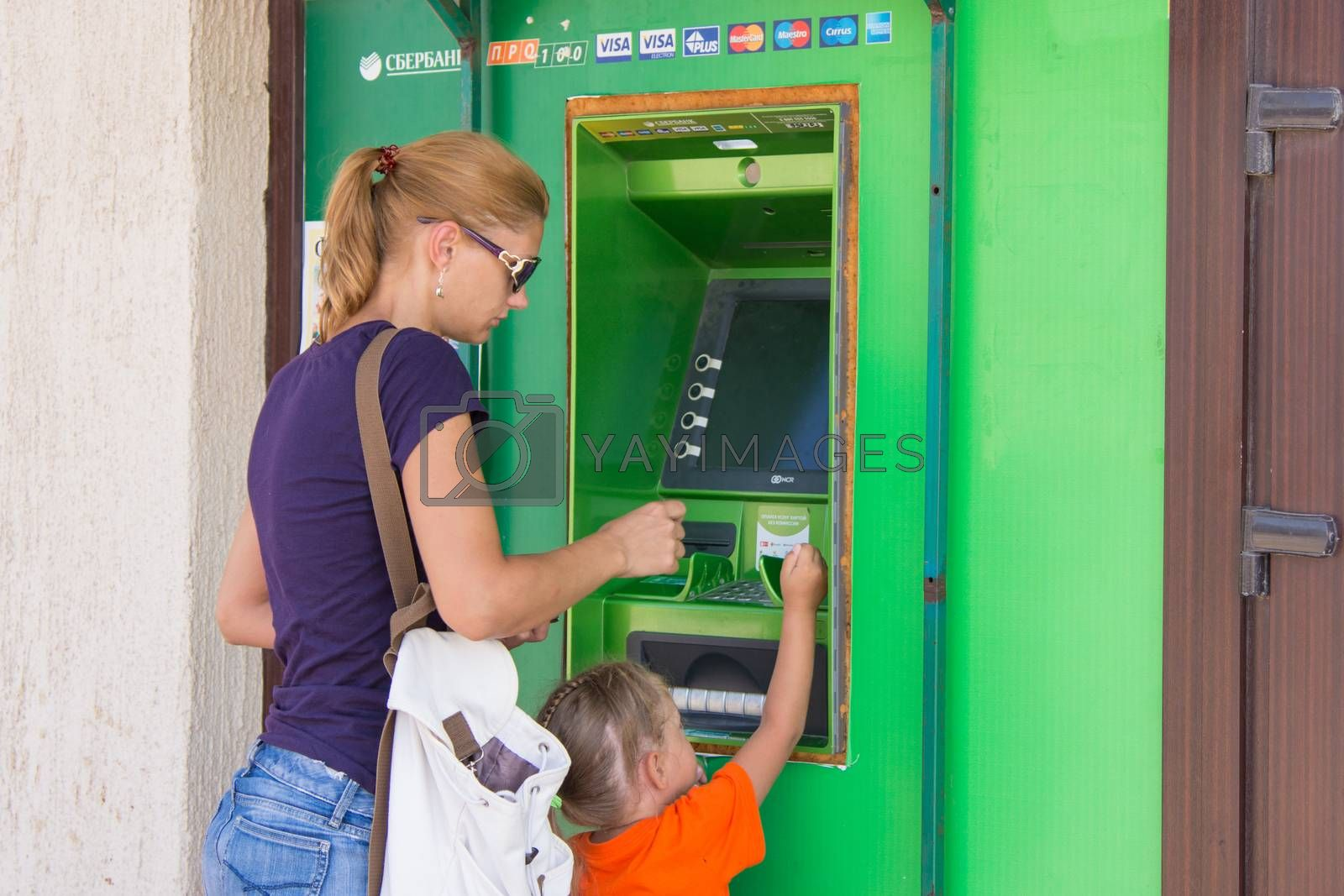 Anapa, Russia - September 20, 2015: A young girl with the child to withdraw money from the ATM Sberbank