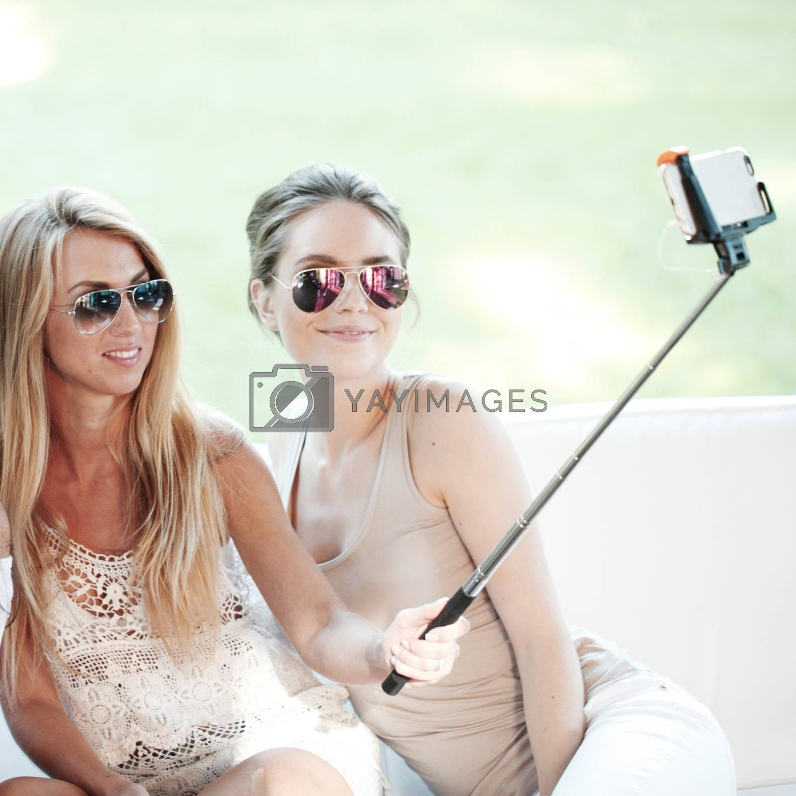 Young beautiful female friends taking selfie outdoors
