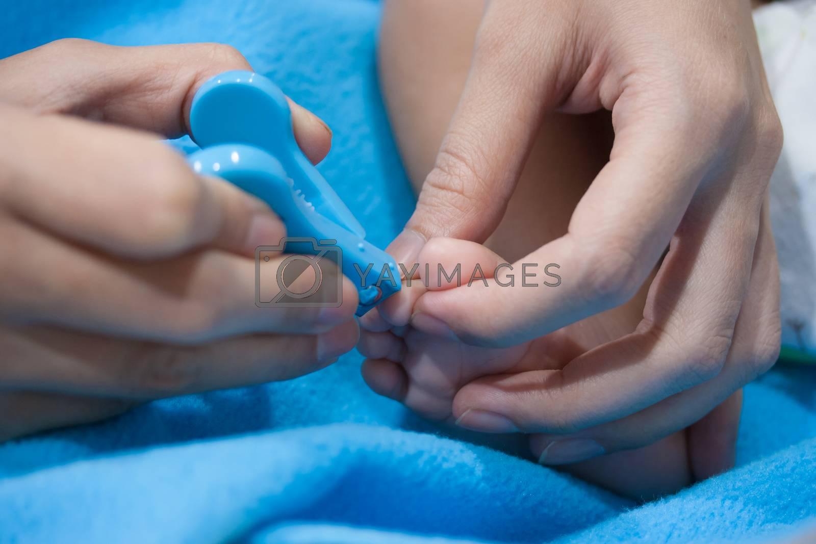 Close up of mum cutting babies nails