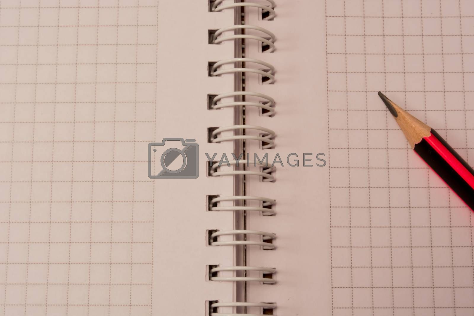 White empty notebook with pencil on top of it.