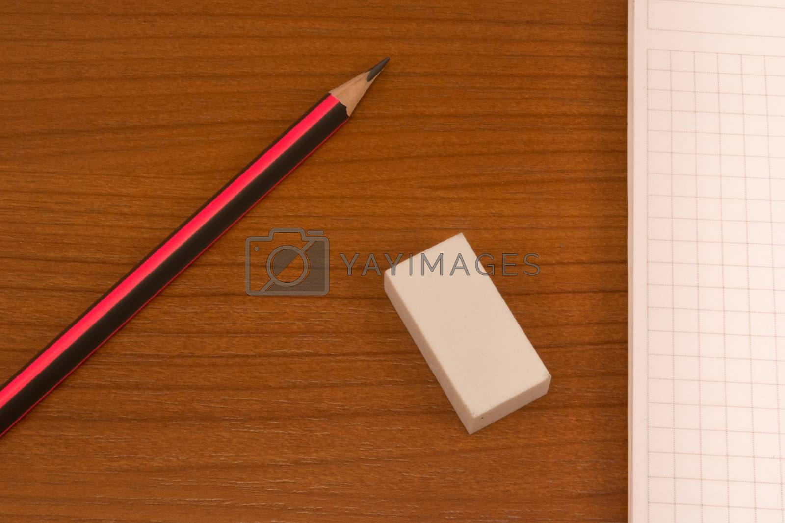 Wooden table with pencil, notebook and eraser