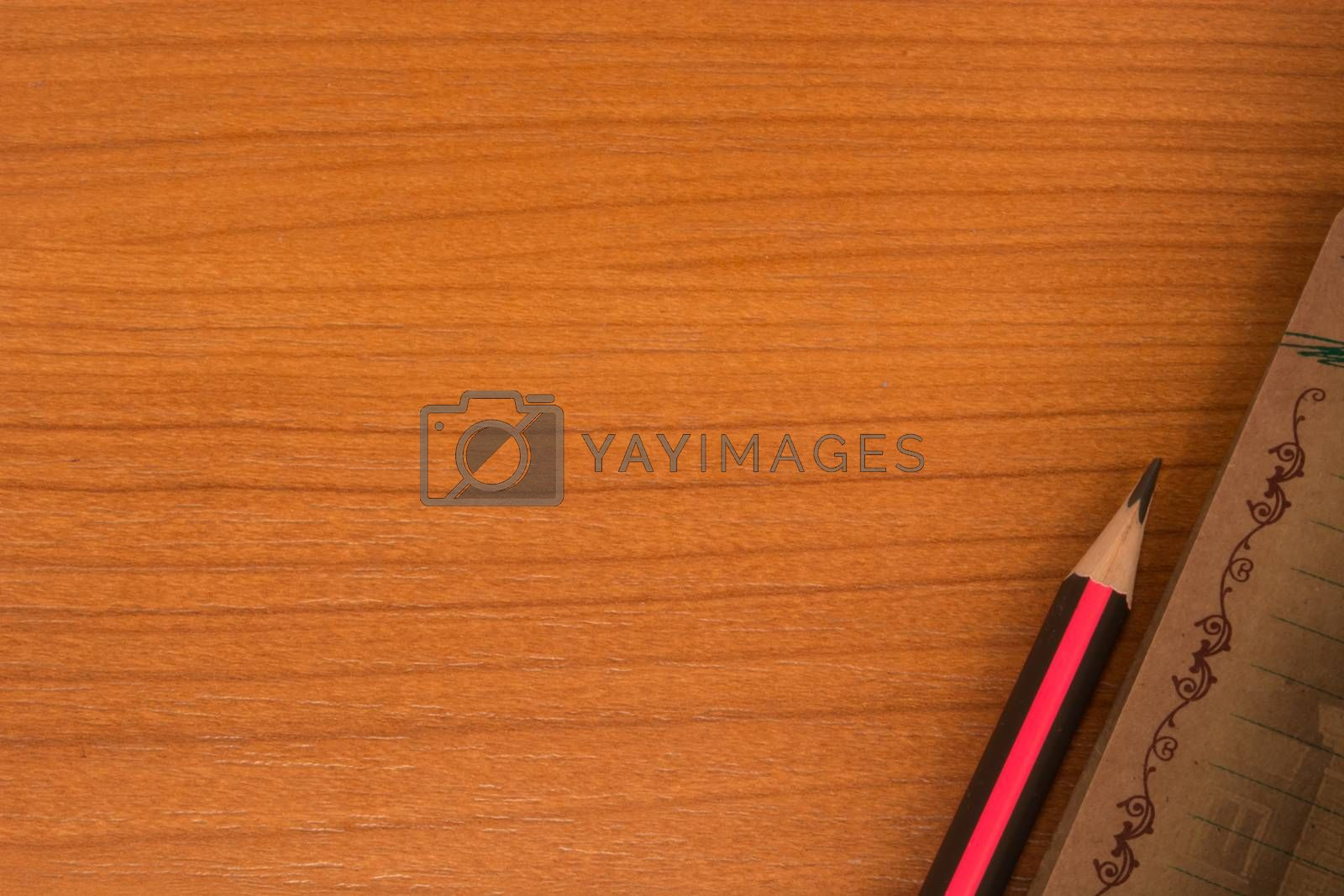 Wooden table with notebook and pencil in one corner