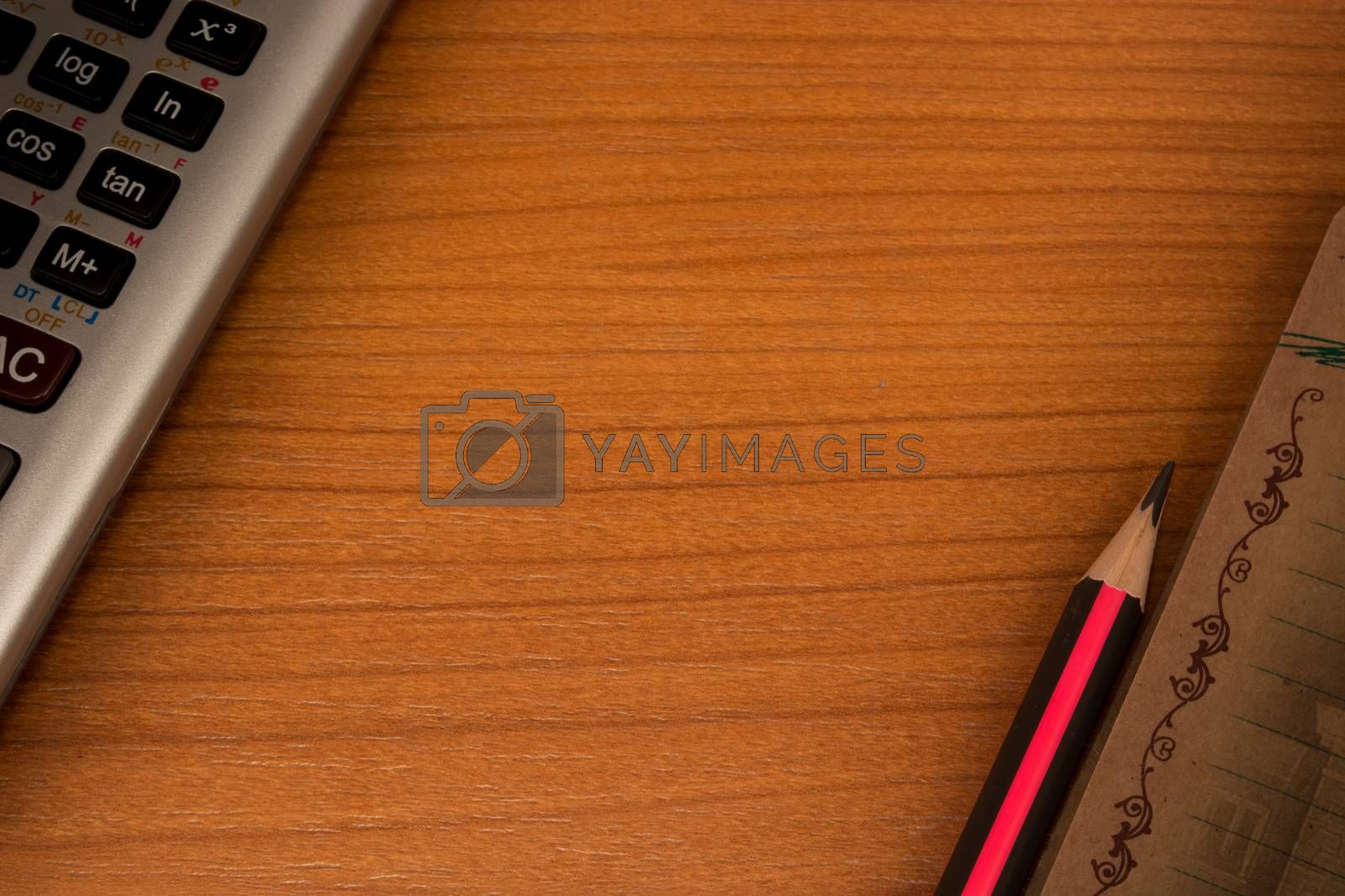 Wooden table with calculator in one corner and pencil and notebook in another