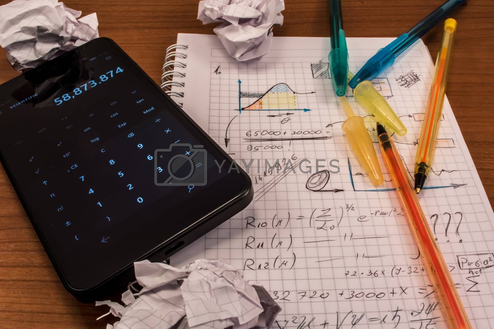 Notebook full of mathematics. Smart phone, pencils and crumpled paper are visible