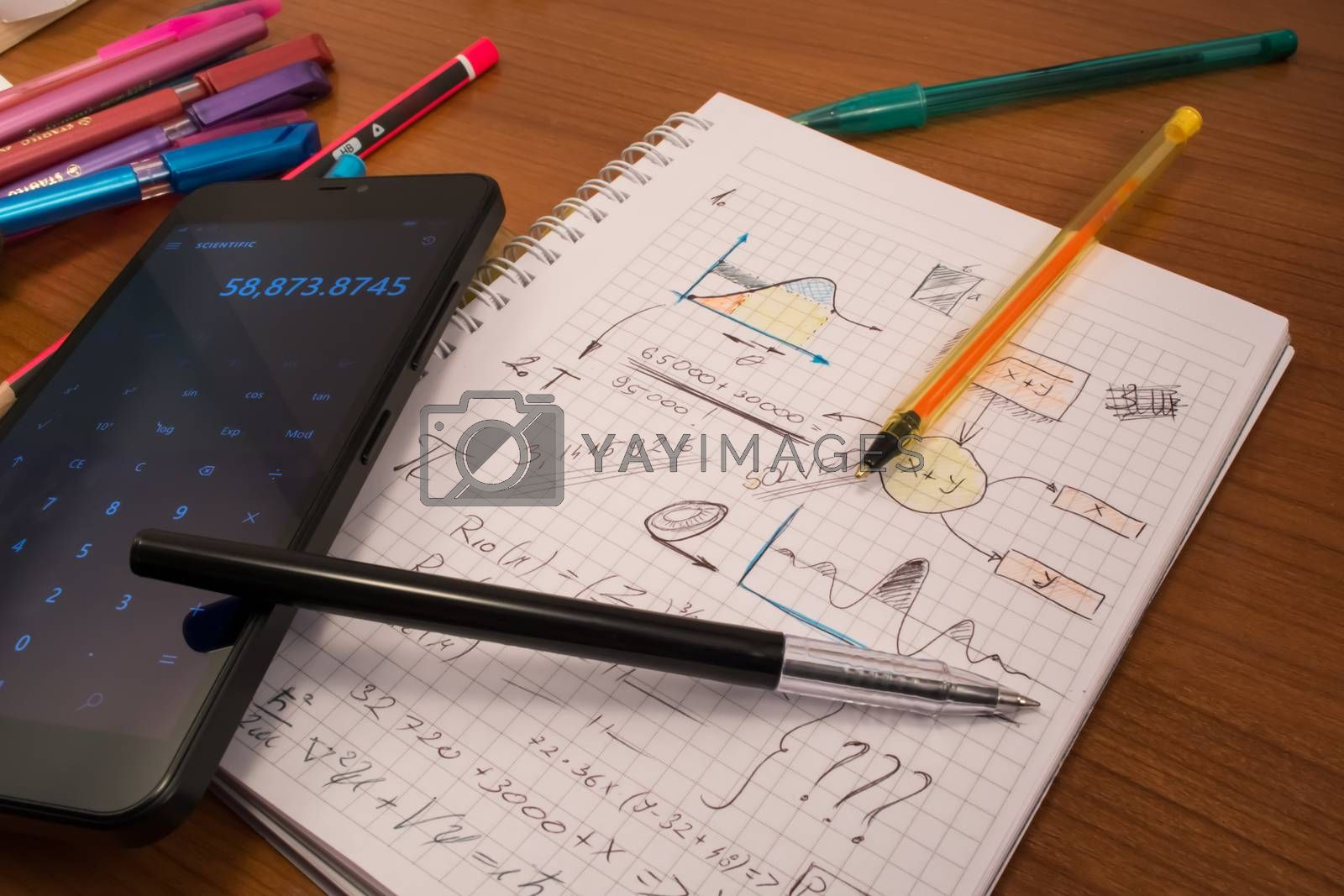 Notebook full of mathematics. Smart phone and pencils are visible