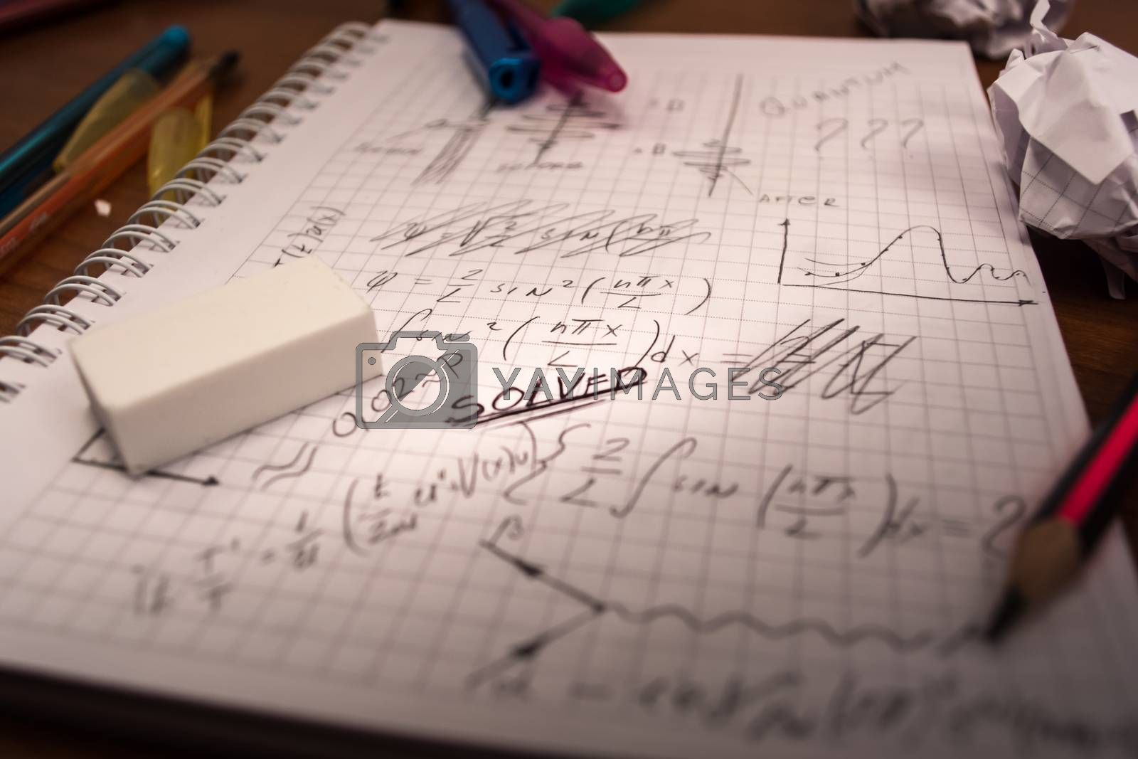 Notebook full of written formulas with pencil and eraser on top of it. Crumpled paper all around the table
