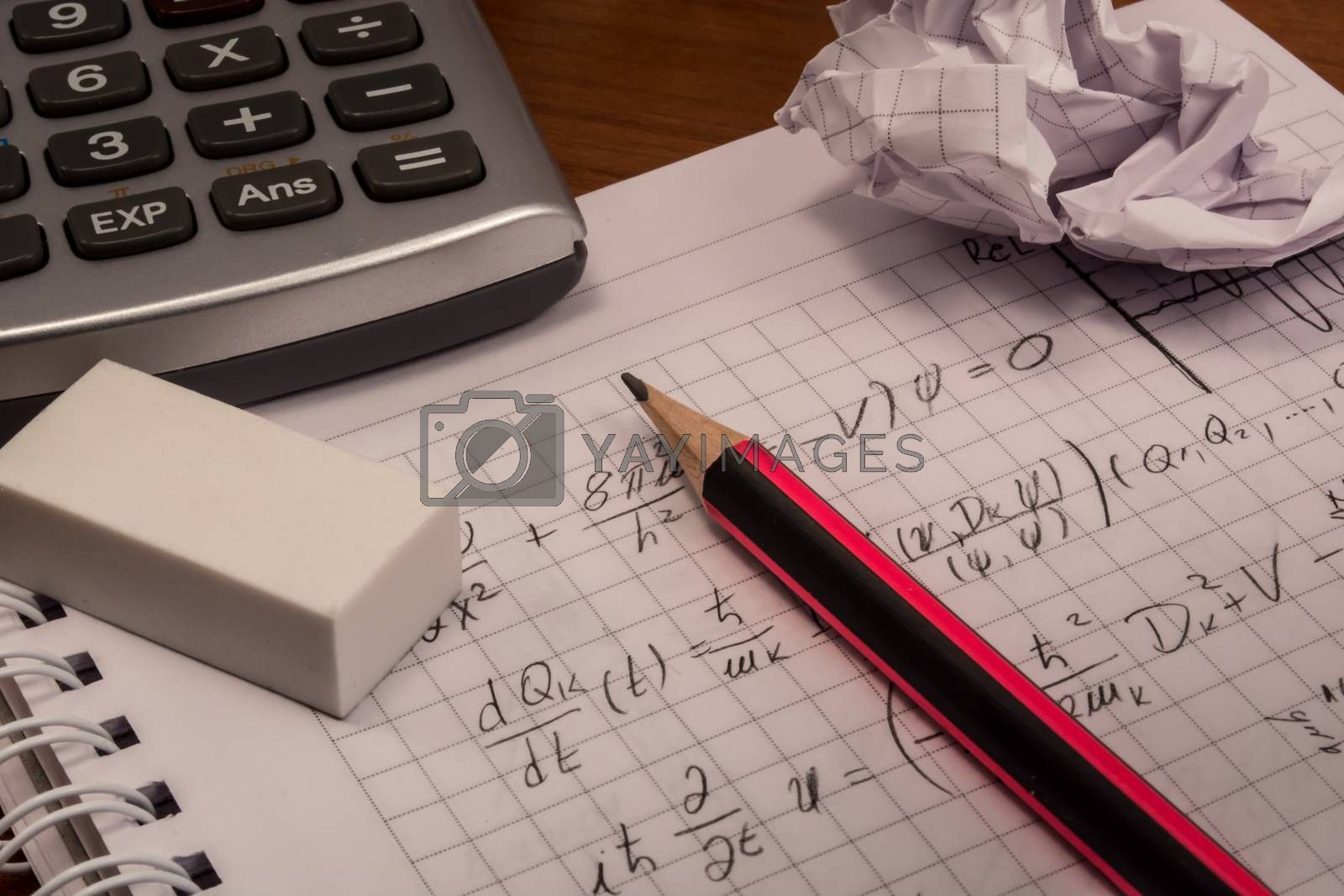 Messy table with notebook, pencils, crumpled papers and calculator