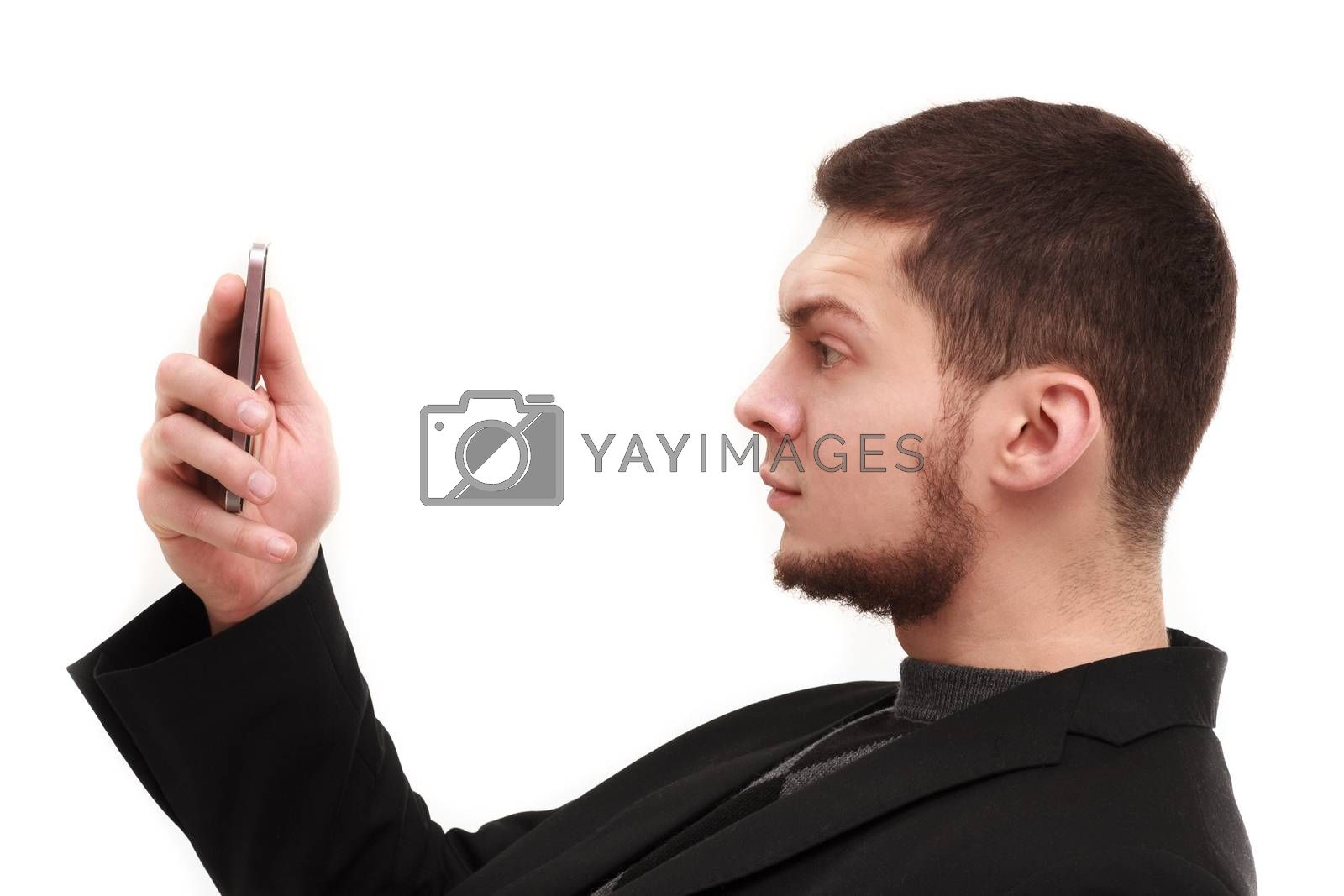 Businessman with a raised eyebrow using his phone screen isolated on white