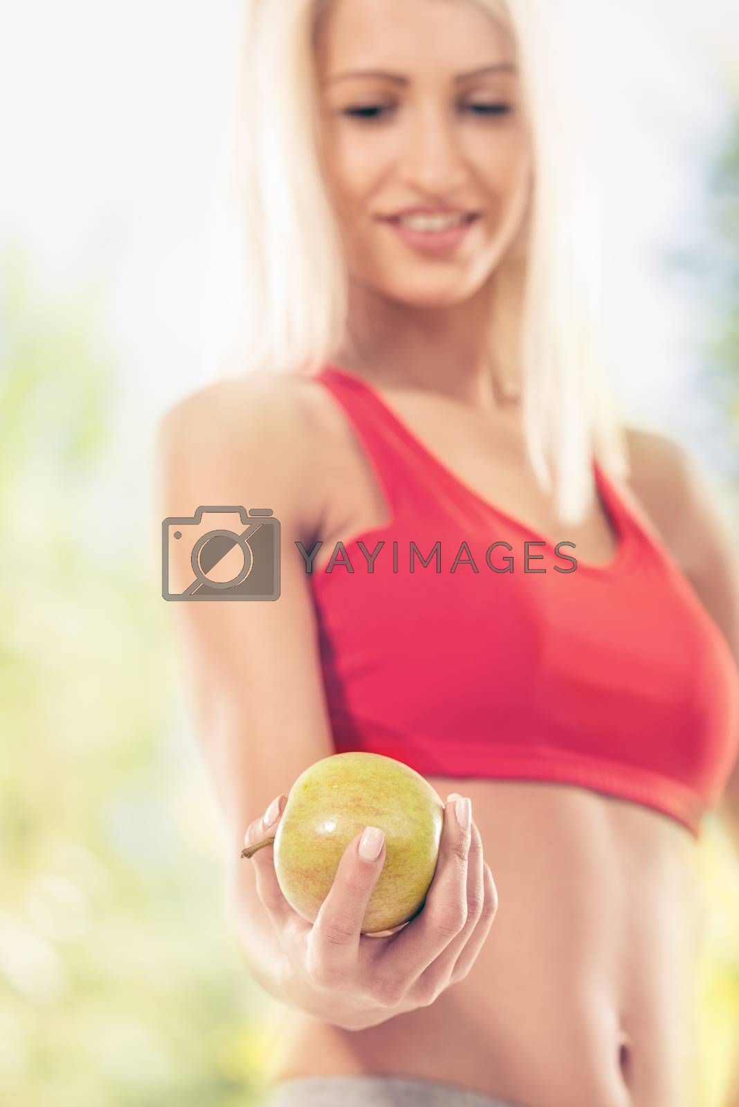 Woman holding apple. Focus on apple. Dieting concept.