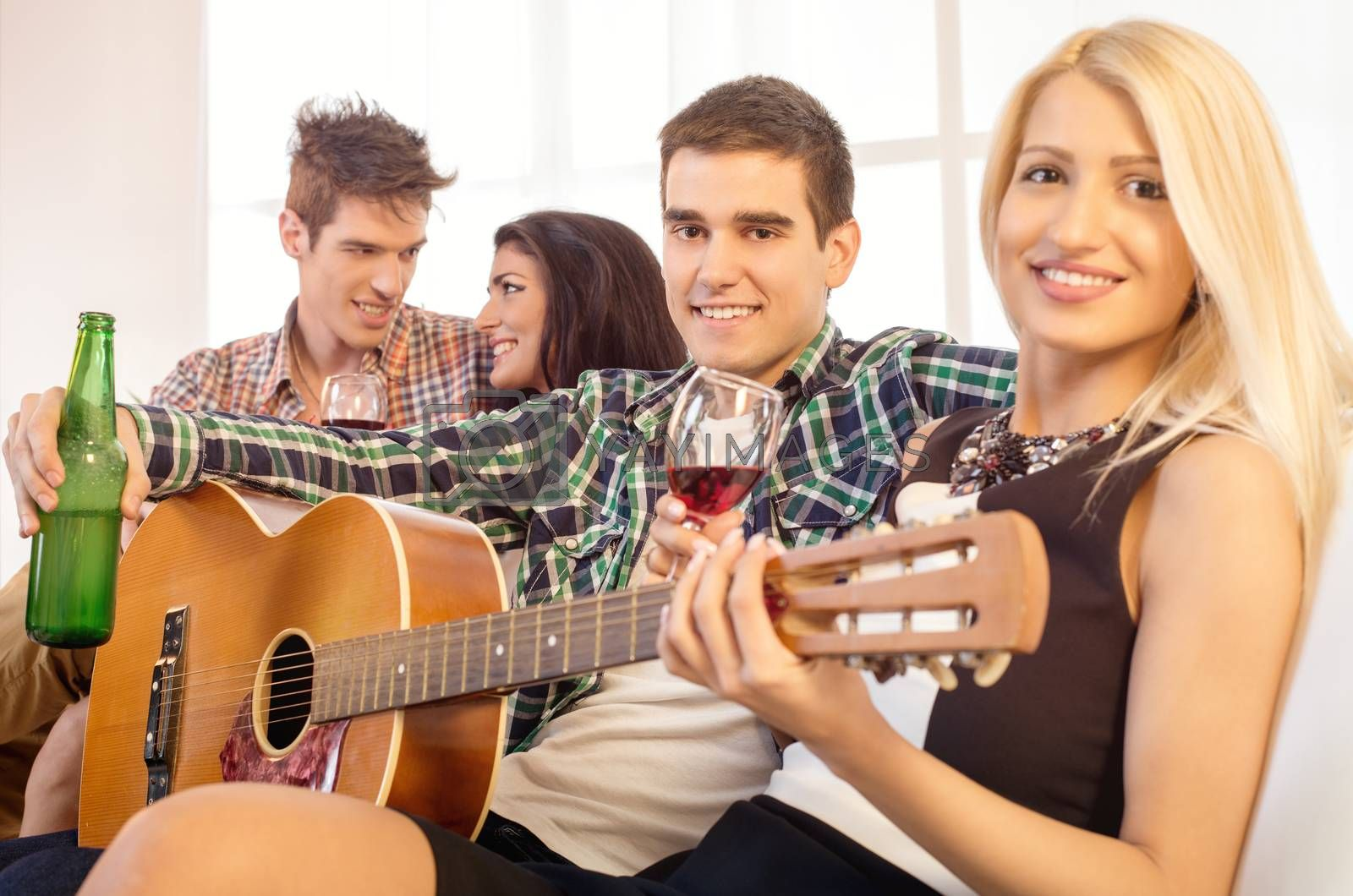Small group of happy young people hang out at the house party with an acoustic guitar.
