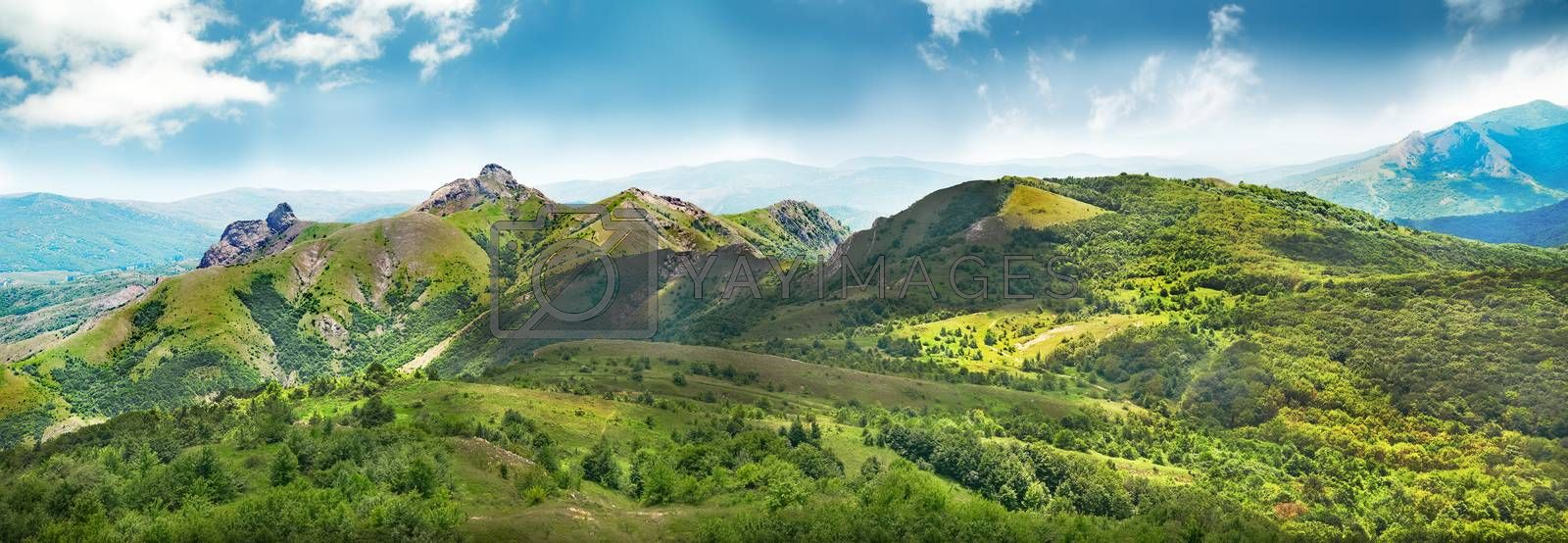 Green mountains covered with forest on the blue sky background. Panorama