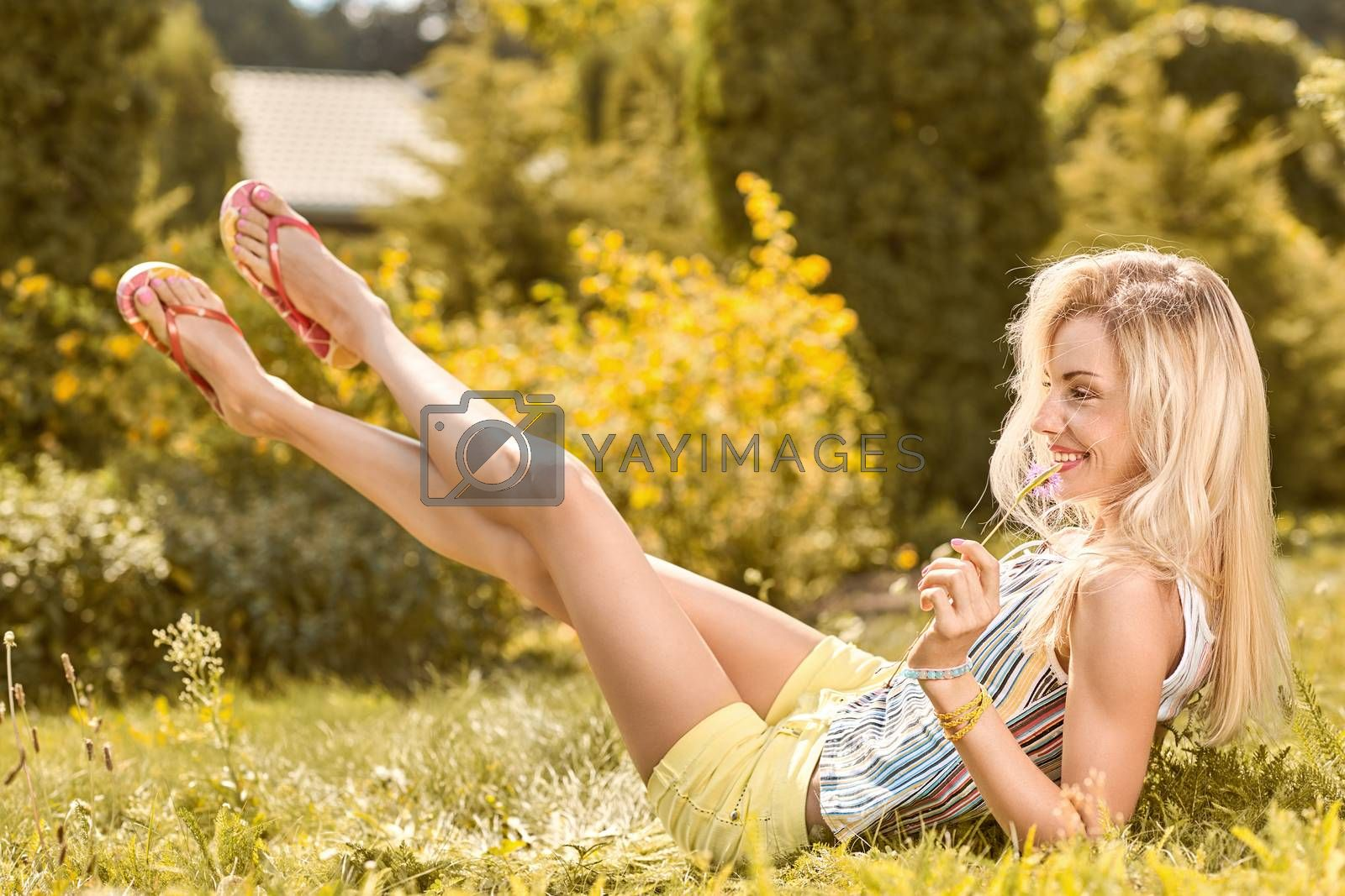 Beauty playful woman relax in summer garden smiling on grass, people, outdoors, bokeh. Attractive happy blonde girl enjoying nature, harmony on meadow, lifestyle. Sunny day, forest, flowers, copyspace