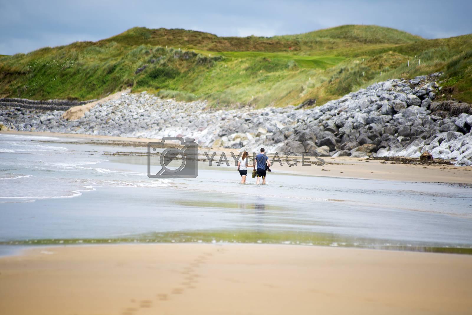 loving couple with dog paddeling on ballybunion beach