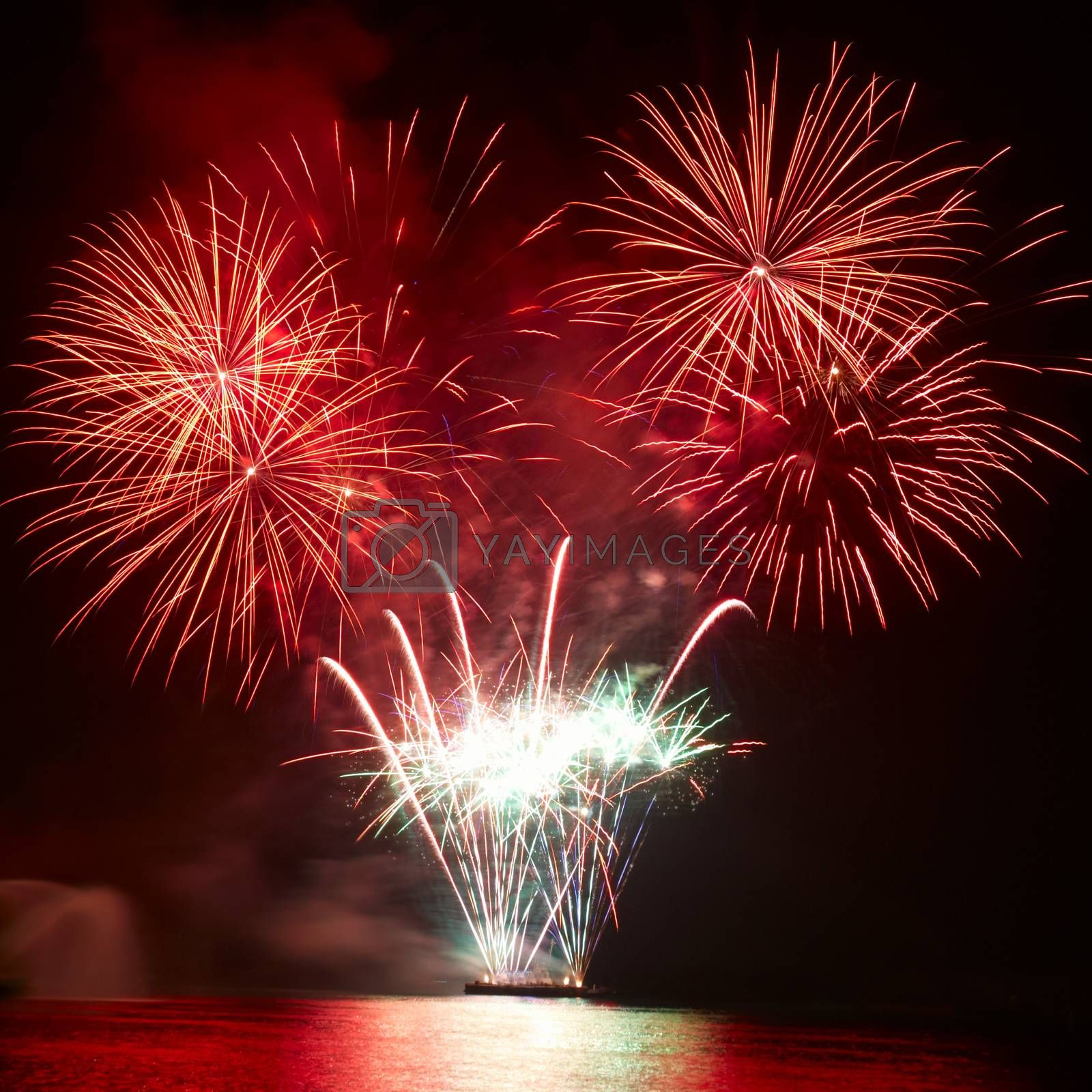Beautiful colorful red and orange holiday fireworks on the black sky background