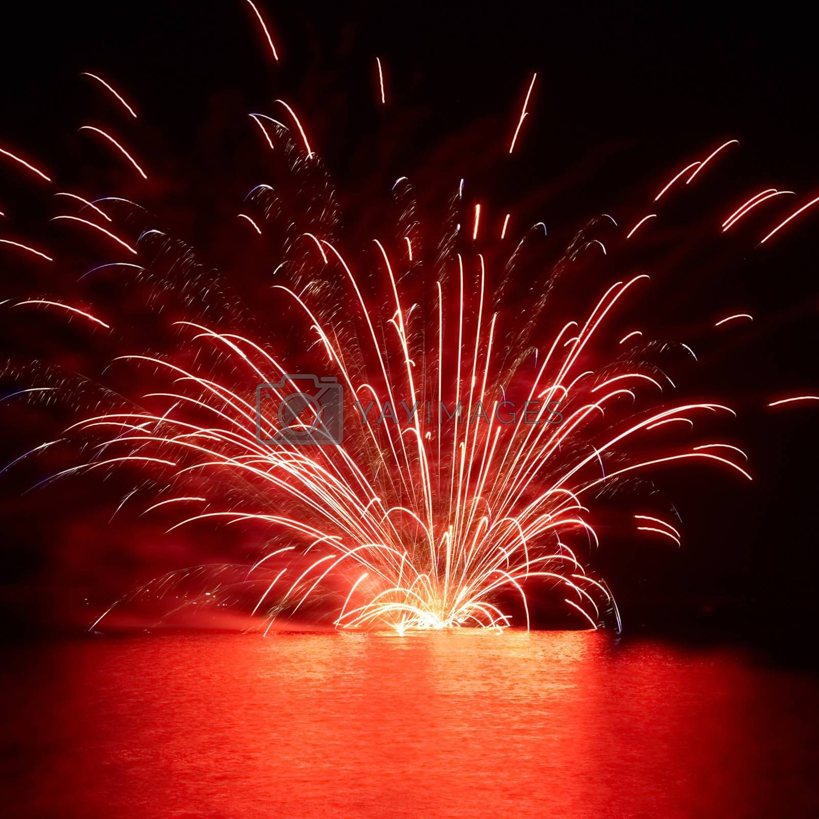 Red holiday fireworks on the lake with black sky background