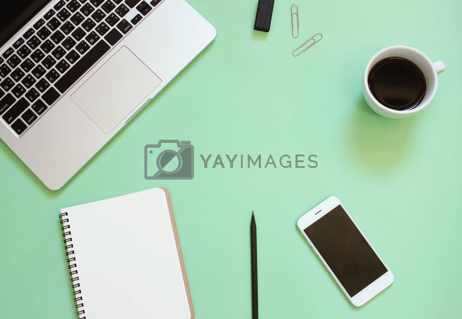 Creative flat lay design of workspace desk with laptop, blank notebook, smartphone, coffee, stationery with copy space background