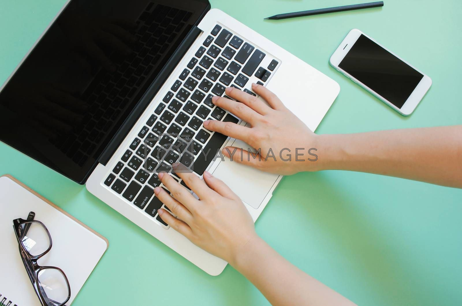 Hand using laptop on creative flat lay workspace desk with smartphone and stationery on green background