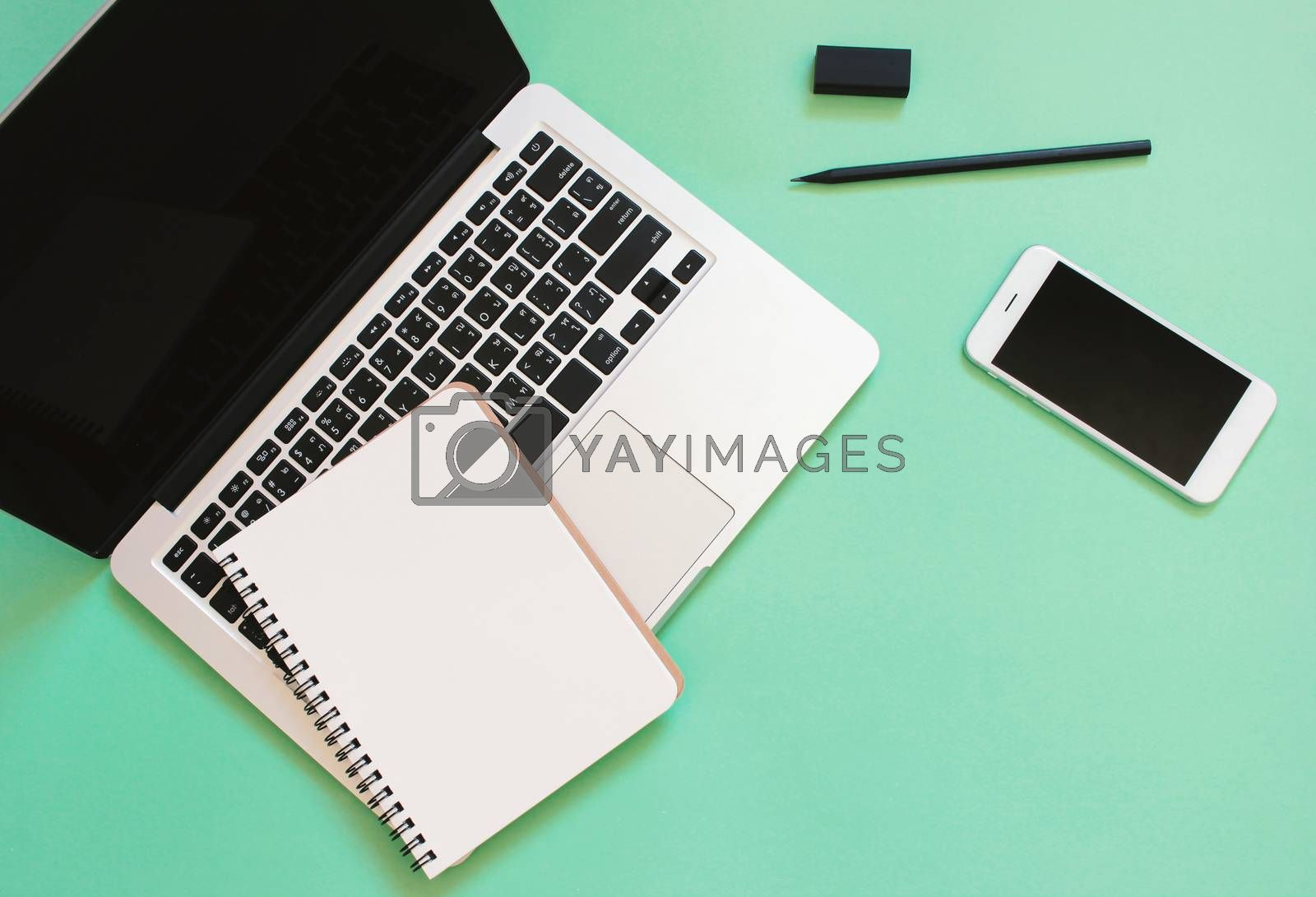 Creative flat lay design of workspace desk with laptop, blank notebook, smartphone and stationery with copy space background