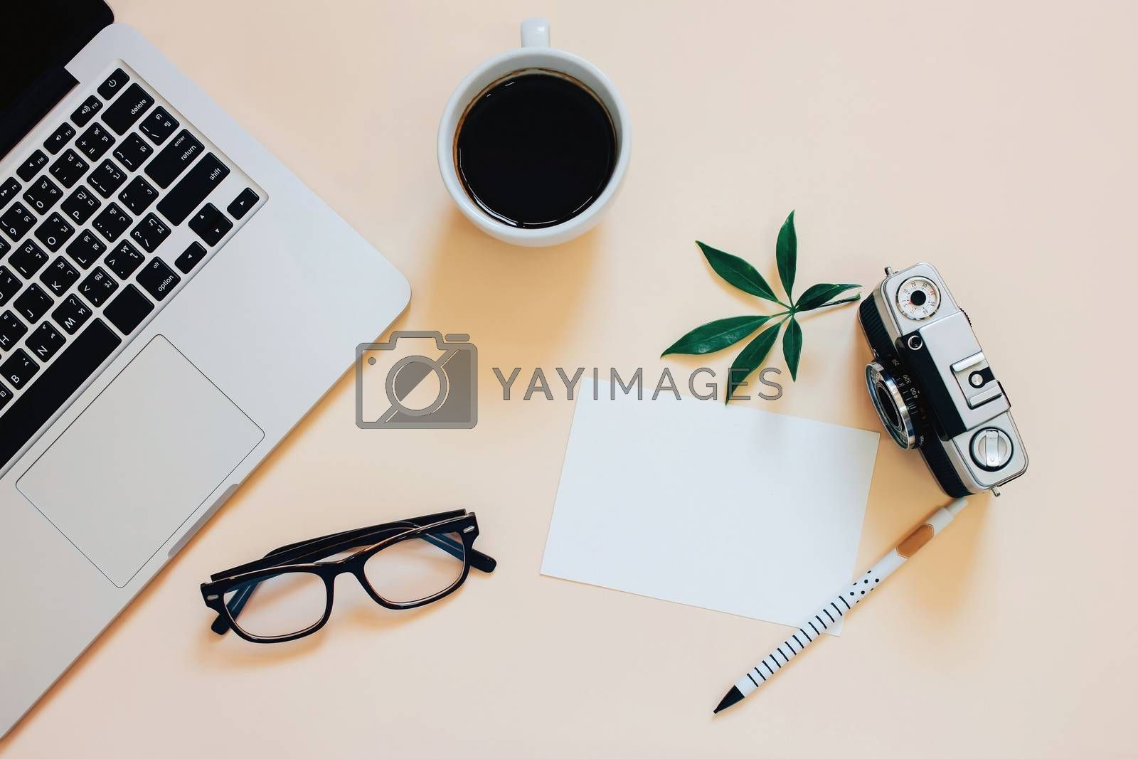Creative flat lay photo of workspace desk with laptop, coffee, blank paper and film camera with copy space background, minimal styled
