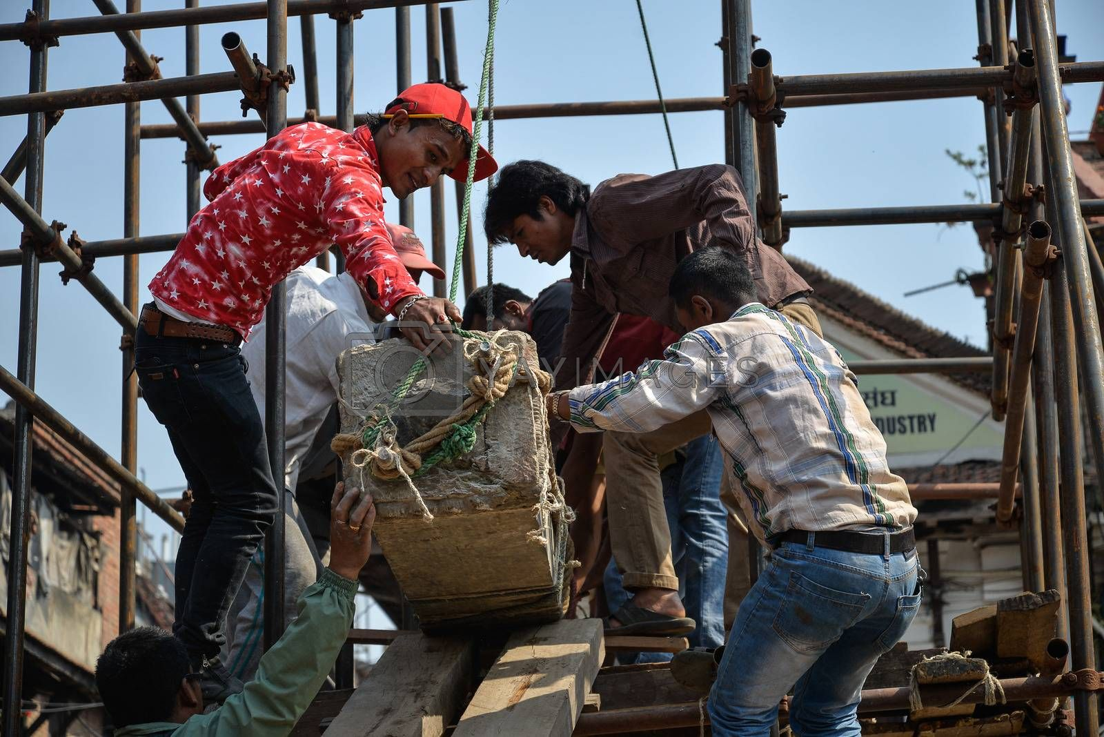 NEPAL, Kathmandu: Men begin rebuilding heritage sites damaged by the earthquake a year ago, on April 25, 2016, at Patan Durbar Square in Kathmandu, in Nepal, during the first anniversary of the quake.Some 9,000 people were killed in the 7.8-magnitude quake that struck April 25, 2015 and its aftershocks. .