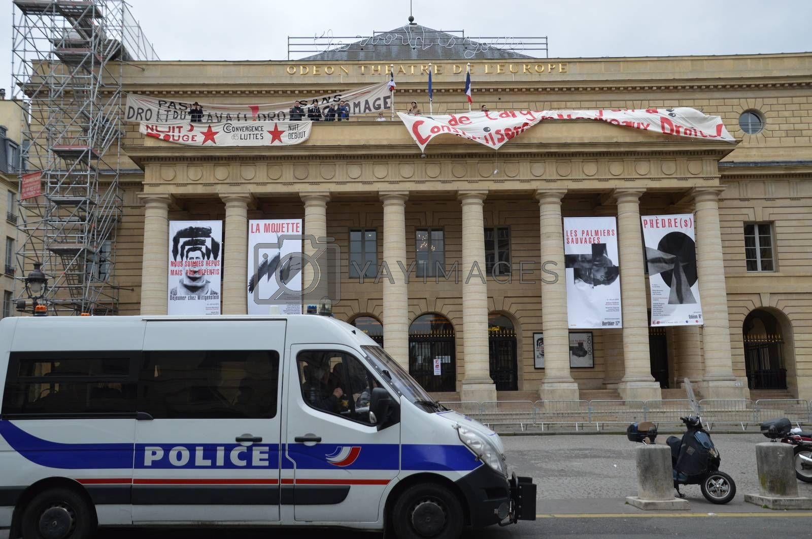 FRANCE, Paris : Policemen stand guard outside the Odeon theatre as French artists and entertainment workers known in France as intermittents du spectacle occupy the building and display a banner reading There is money, let's build new rights in Paris on April 25, 2016. Around 50 people occupied the building to protest against the French government's proposed labour reforms and to demand the reshaping of the unemployment insurance before the start of the unemployment insurance negotiations, as part of a protest in conjunction with the Nuit Debout (Night Rising) movement against the French government's proposed labour reforms.