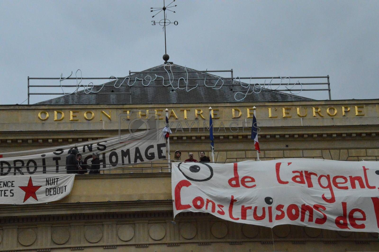 FRANCE, Paris : A man stands by banners reading There is money, let's build new rights displayed on the top of the Odeon theatre as French artists and entertainment workers known in France as intermittents du spectacle occupy the building in Paris on April 25, 2016. Around 50 people occupies the building to protest against the French government's proposed labour reforms and to demand the reshaping of the unemployment insurance before the start of the unemployment insurance negotiations, as part of a protest in conjunction with the Nuit Debout (Night Rising) movement against the French government's proposed labour reforms.