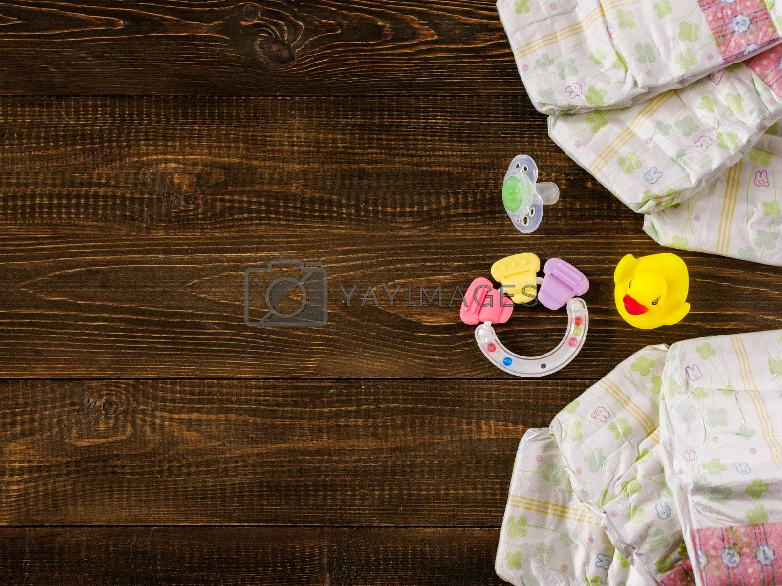 Japanese disposable diapers, teether, dummy and rubber duckling on dark wooden background with copy-space. Flat lay