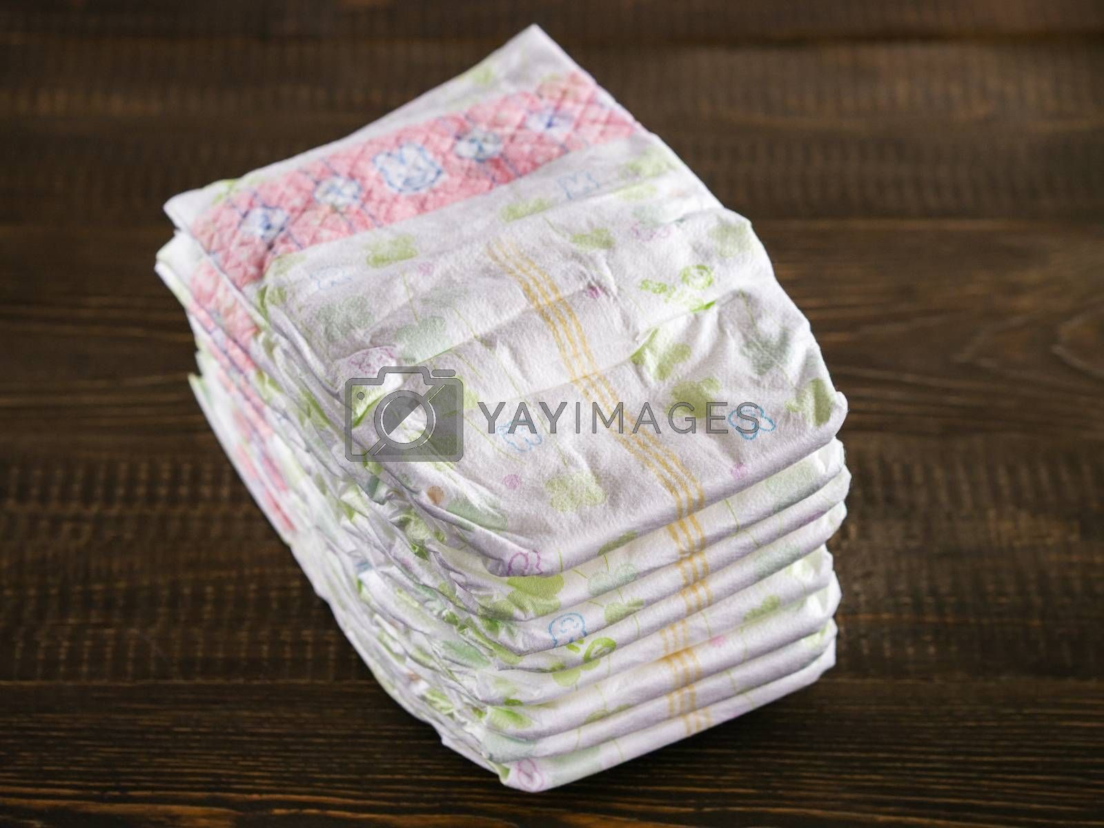 Stack of disposable diapers on a wooded background