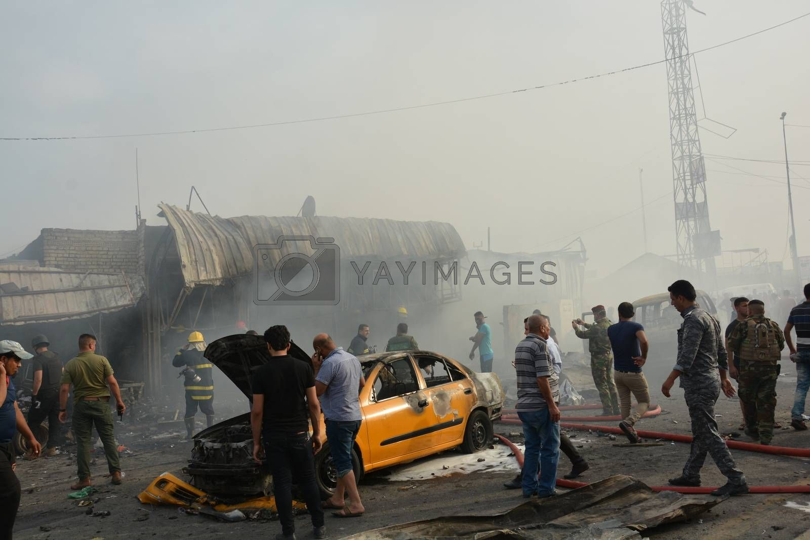 IRAQ, Baghdad: People gather in a predominantly Shi'ite Muslim district of eastern Baghdad as Iraqi security forces and firefighters secure the site of a suicide bombing claimed by the Islamic State group in New Baghdad area, on April 25, 2016. The blast ripped through shops, killing at least eleven people.