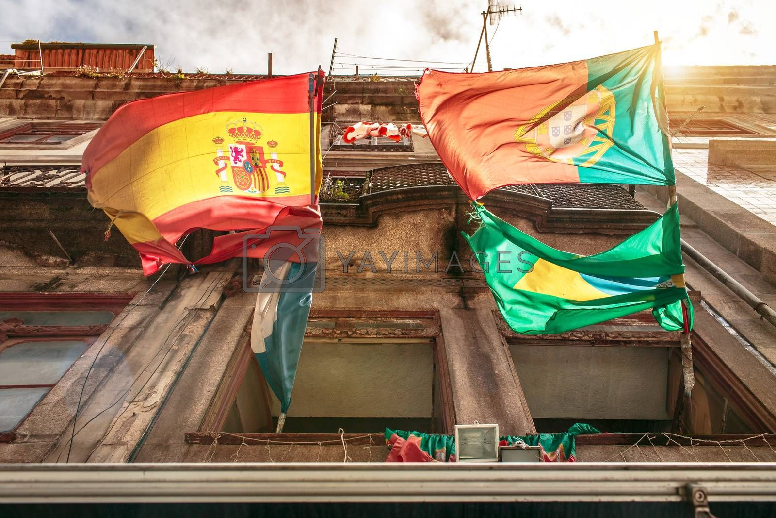 Spanish and Portuguese flags hanging on a building in Porto