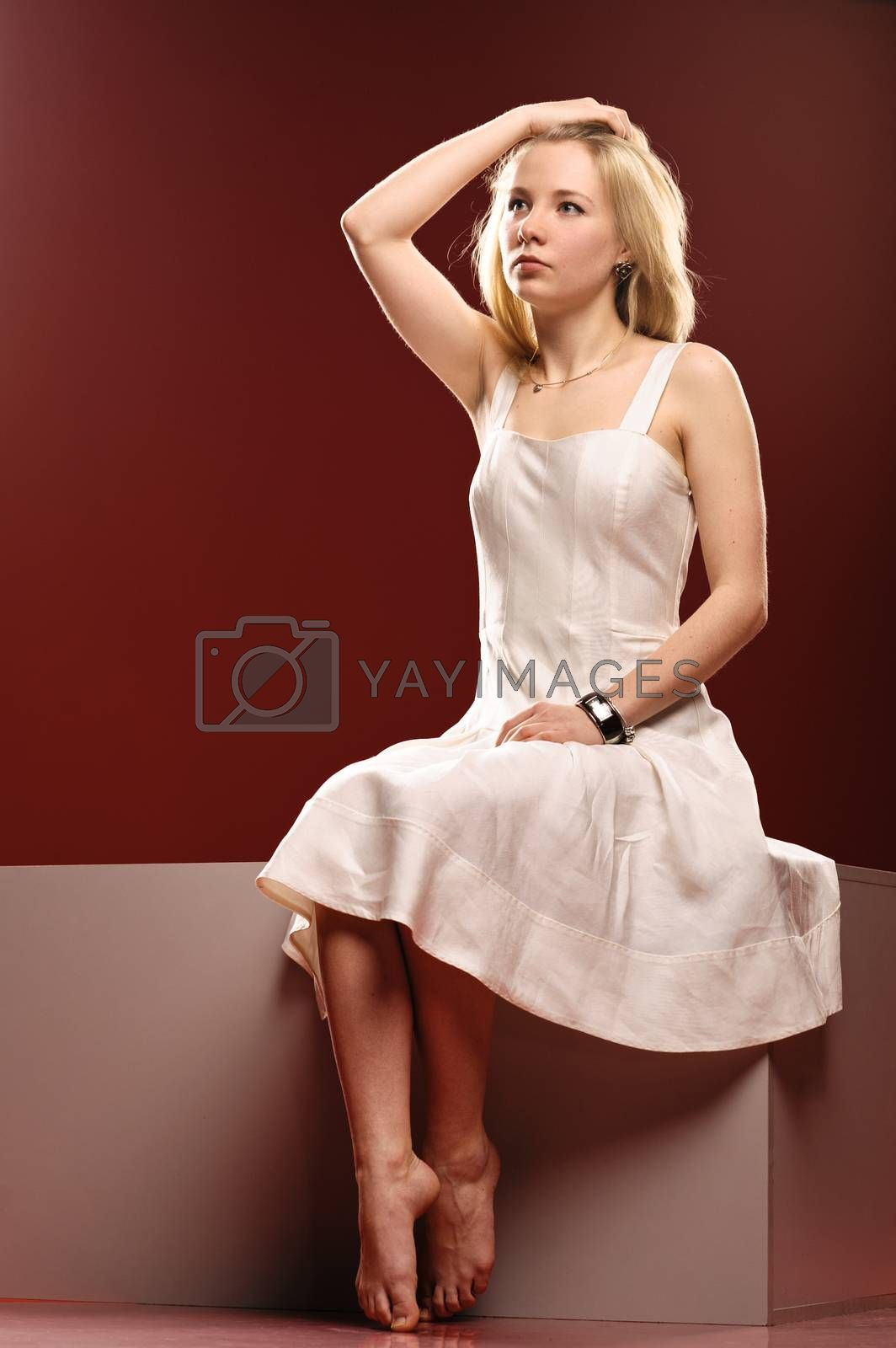 Barefoot girl sitting on a cube isolated on red background