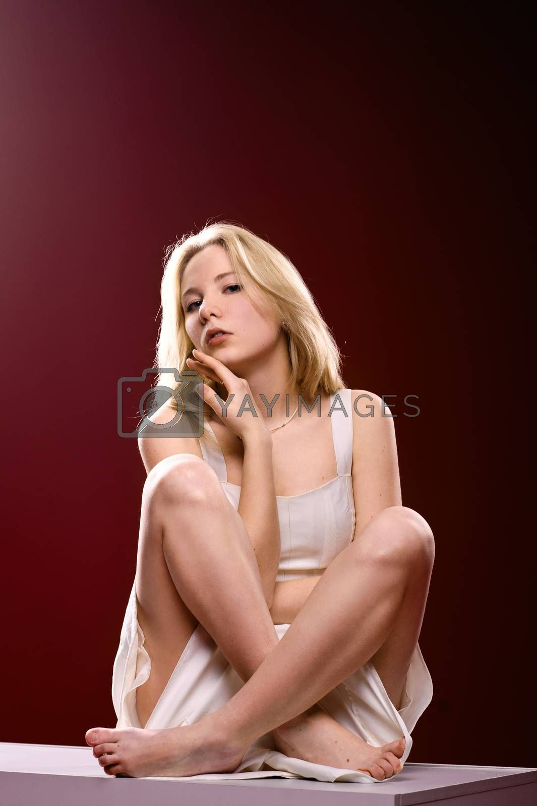 Barefoot girl sitting on a cube with crossed legs isolated on red background