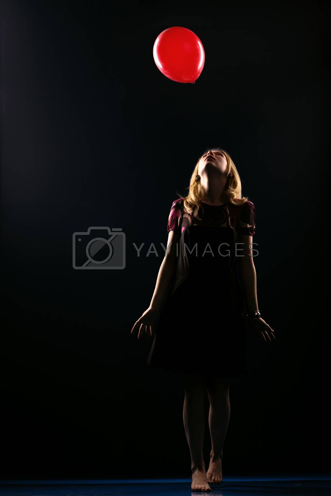 Concept: dream, sadness, hope. Barefoot girl reaching for the flying balloon isolated on black background