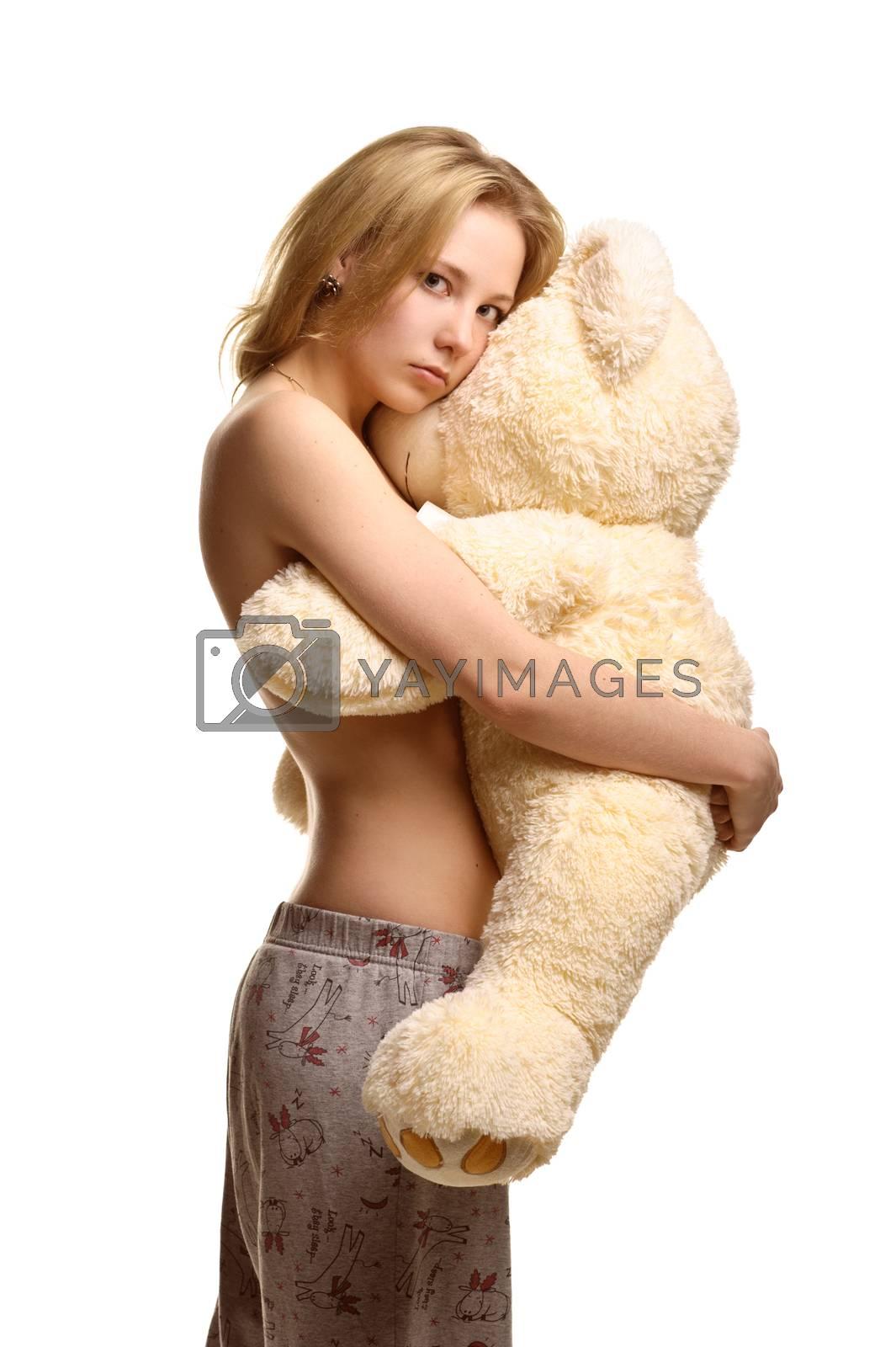 Concept: infantilism, childish, sadness, happiness. Girl in pijamas pants hugging giant plush bear toy isolated on white