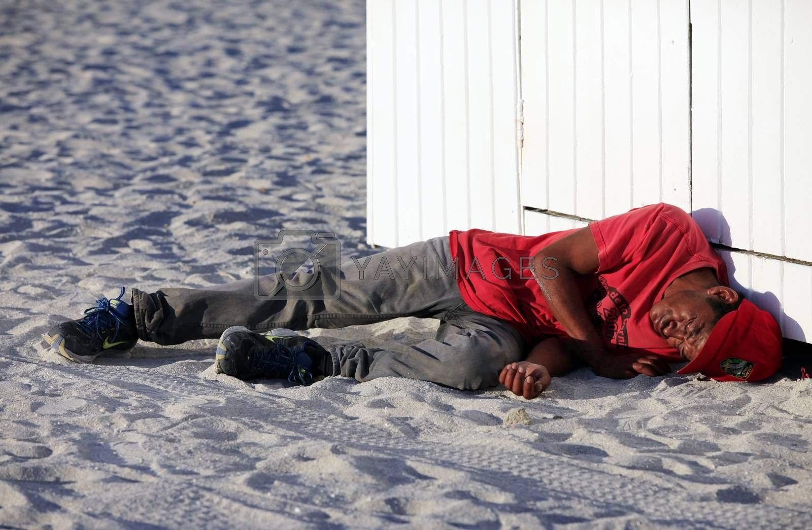 Miami Beach, USA - May 5, 2013: Sleeping homeless drunkard lying on the beach in Miami