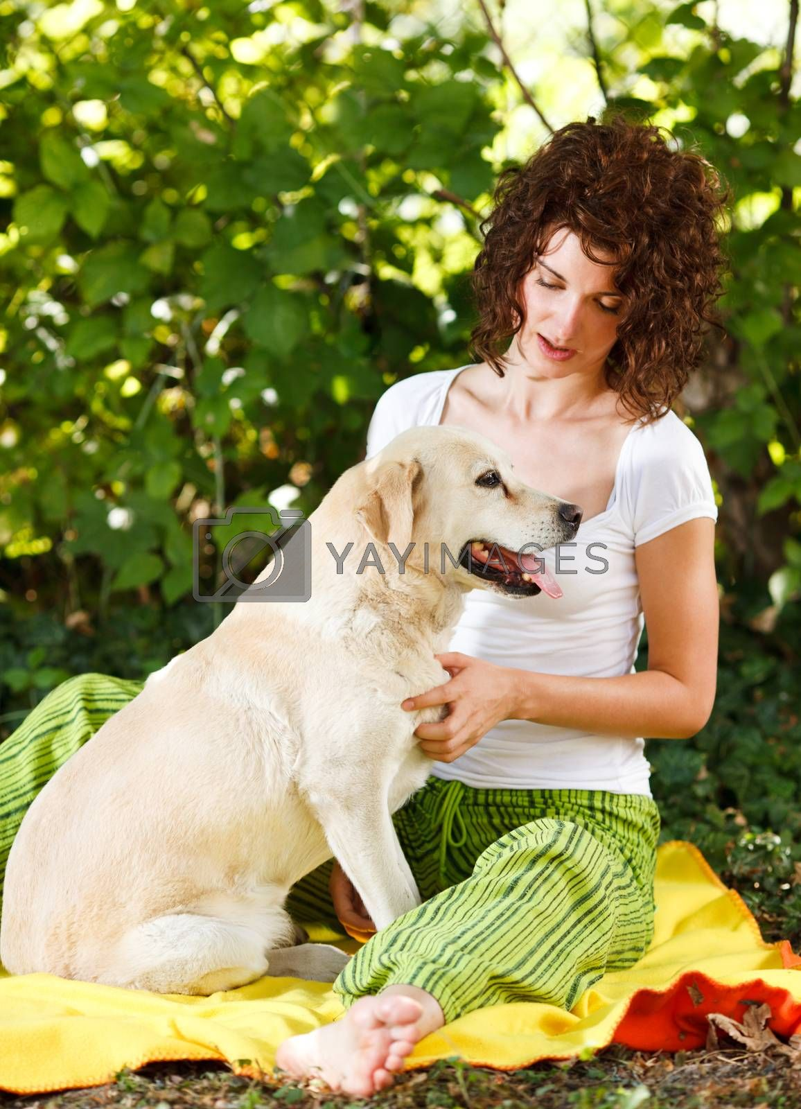 Beautiful young woman and dog in a forest