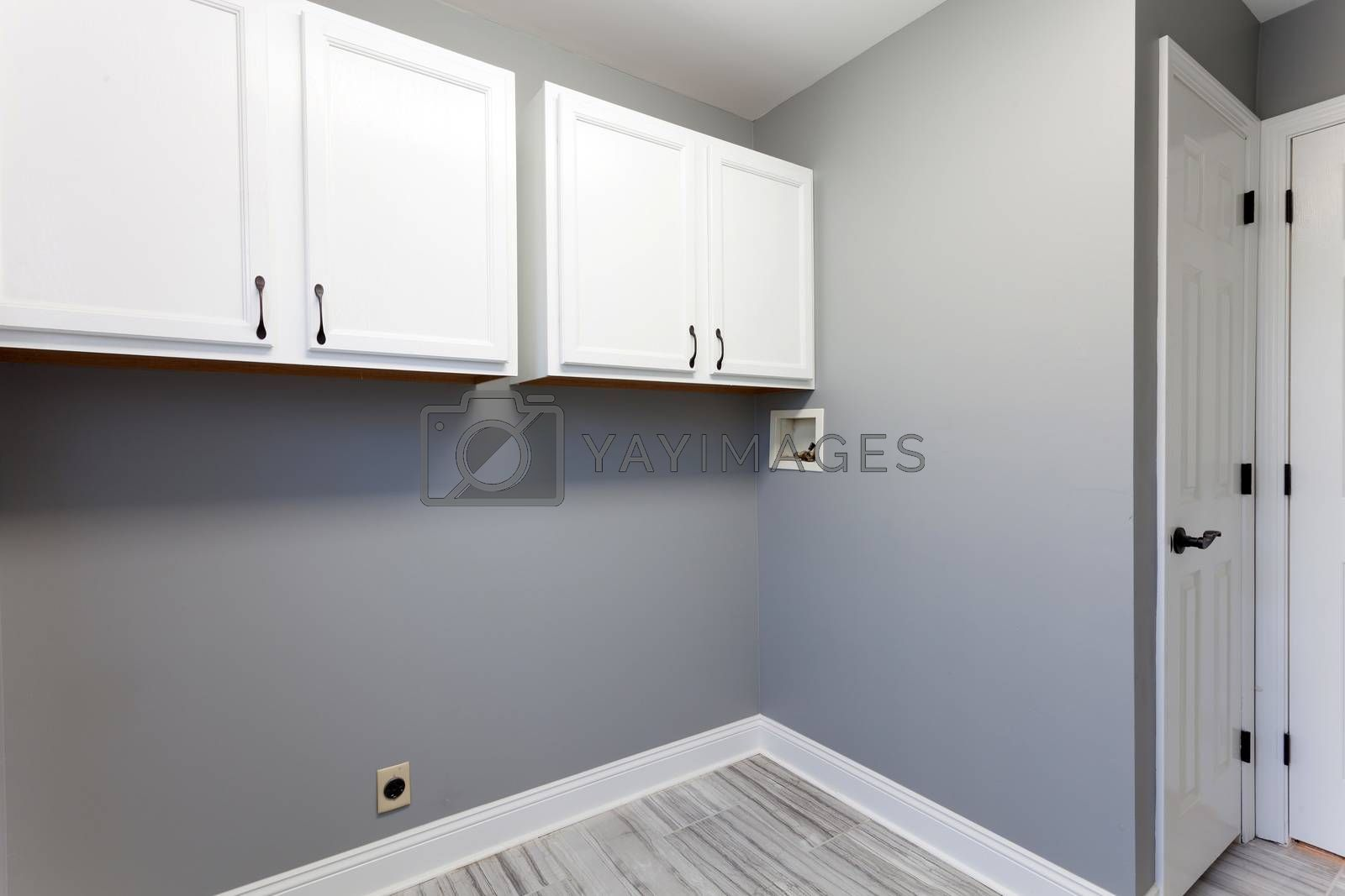 Empty laundry room setup with electrical plumbling hookups and cabinets in a modern home.