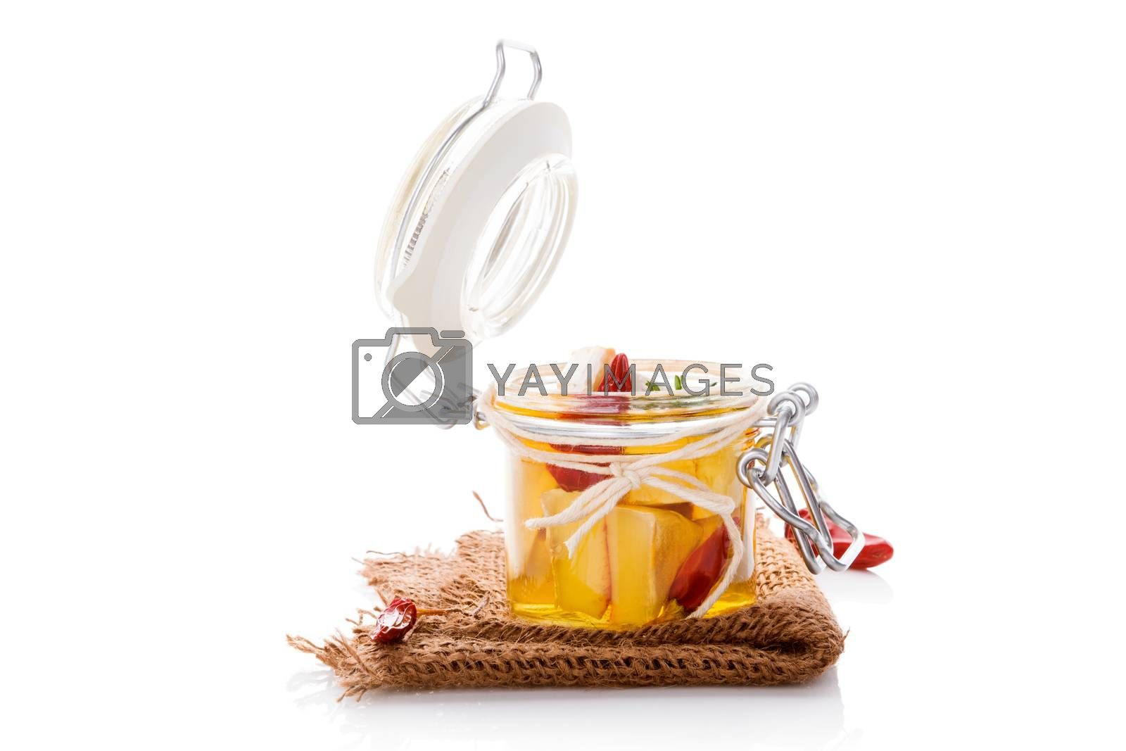 Marinated camembert cheese in glass jar isolated on white background. Culinary cheese eating.
