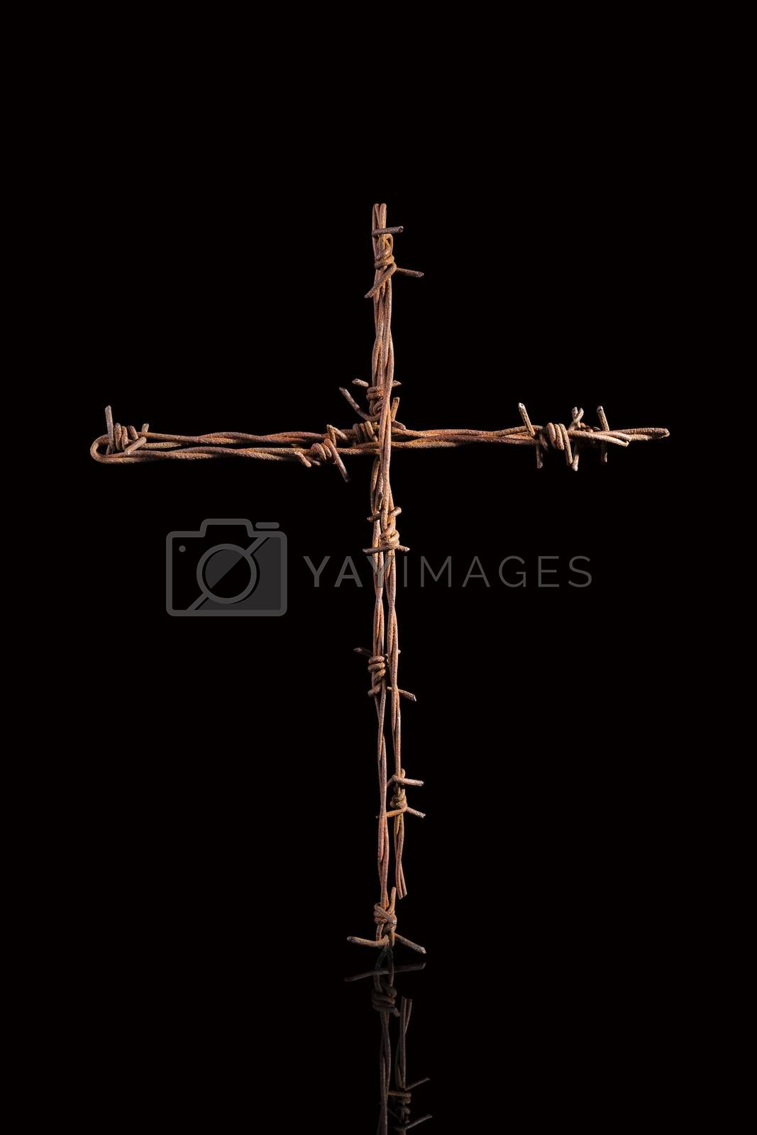 Rusty barbwire cross isolated on black background. Religious war.