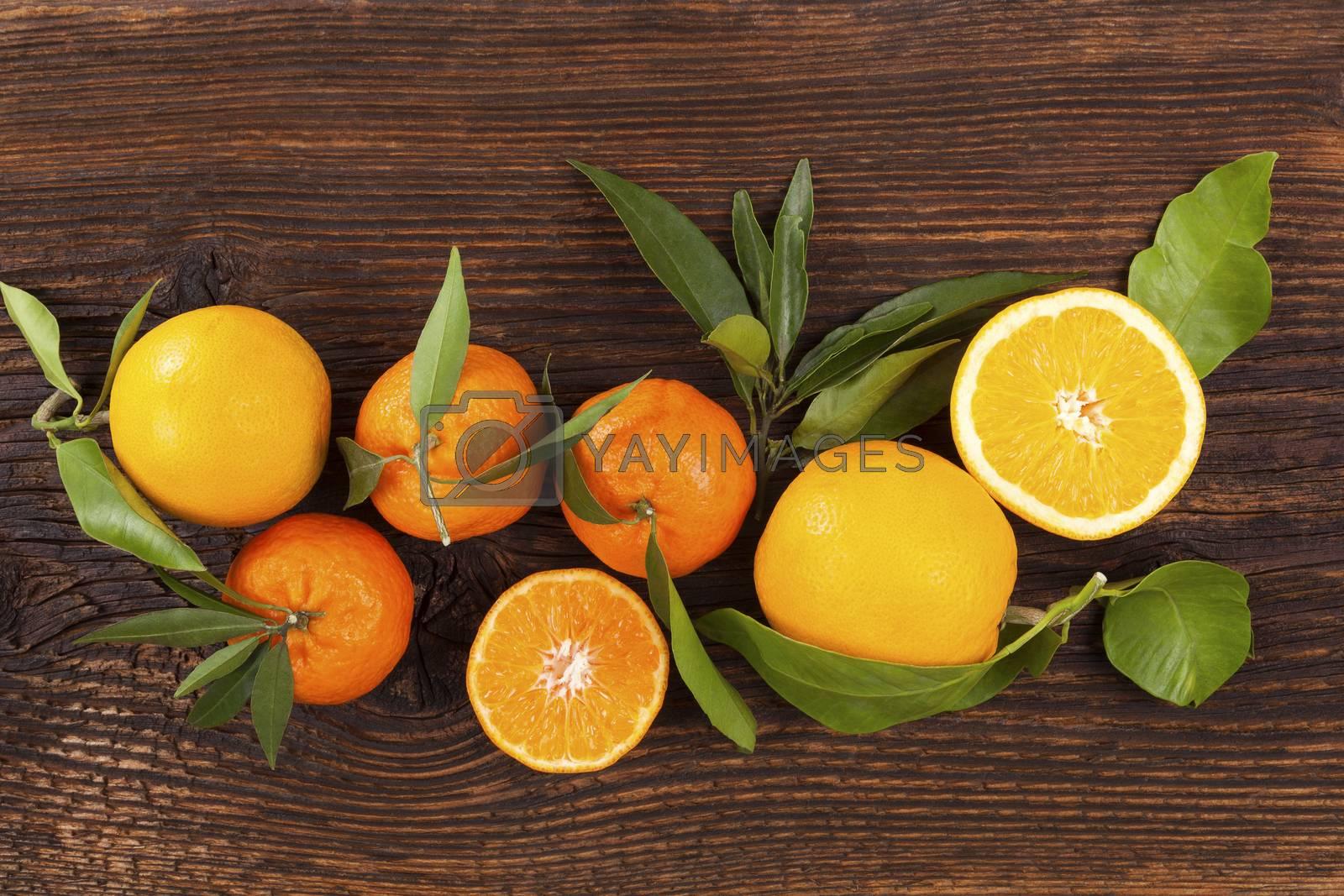 Fresh ripe mandarines with green leaves on wooden table. Organic fresh mandarines, healthy fruit eating.