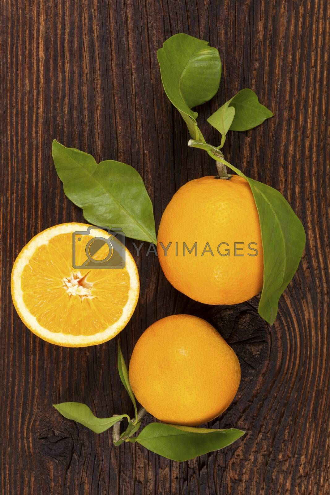 Fresh ripe oranges with green leaves in wooden crate. Organic fresh oranges, healthy fruit eating.