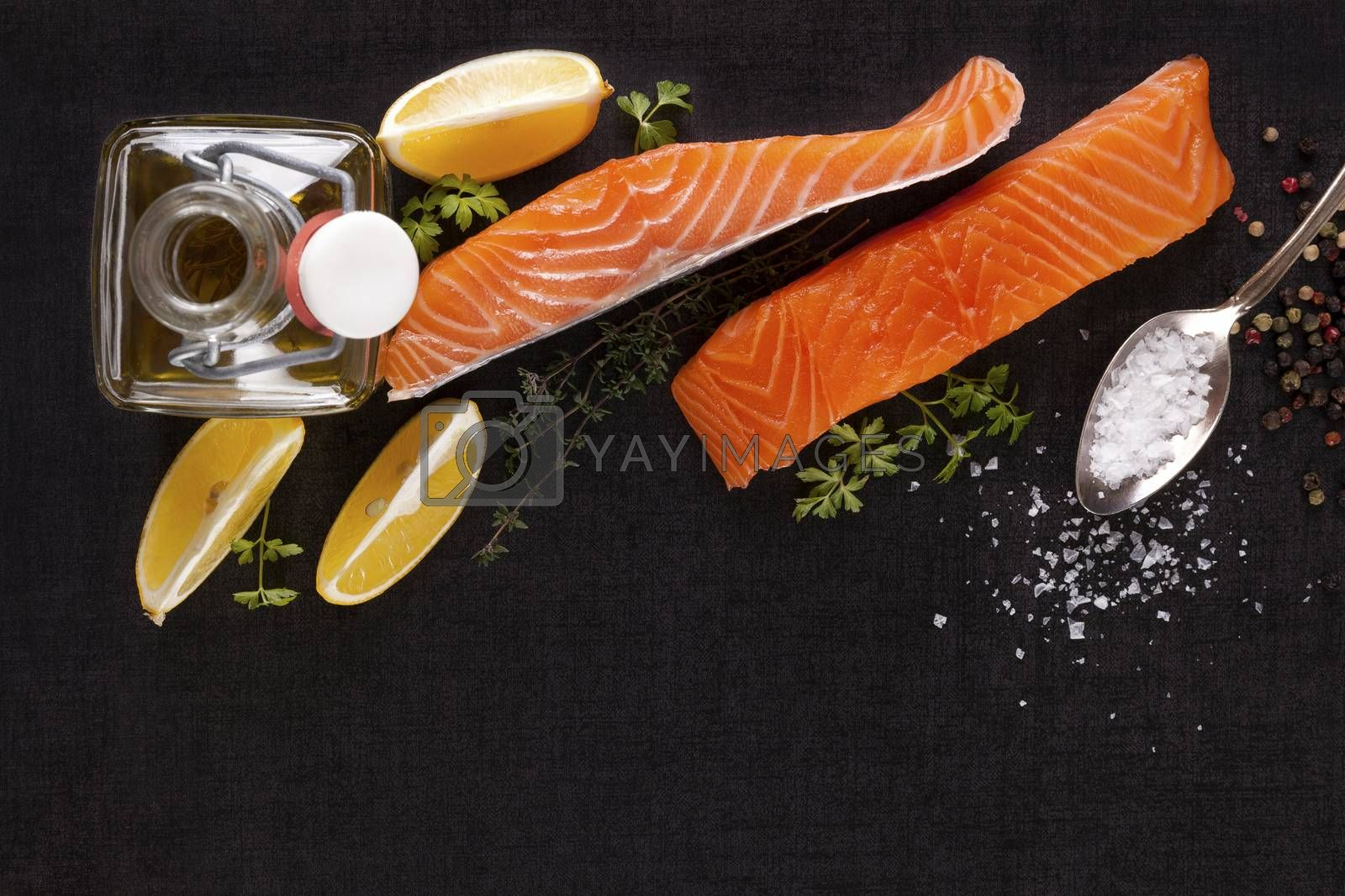 Salmon background with copyspace. Salmon steak, lemon, rosemary and parsley leaf and salt on black background, flat lay.