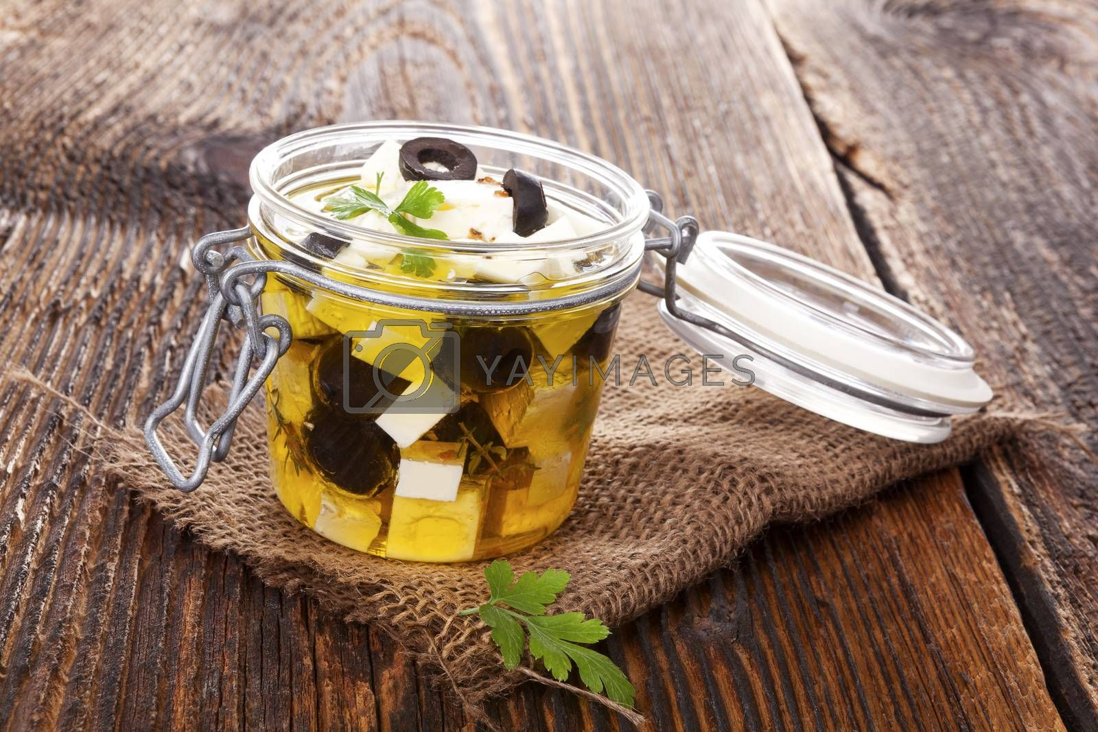 Marinated feta cheese in glass jar on brown wooden background. Culinary marinated cheese, rustic styles.