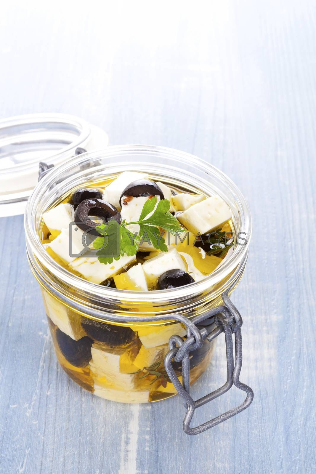 Marinated greek feta cheese in glass jar on blue wooden background. Culinary marinated cheese, rustic styles.