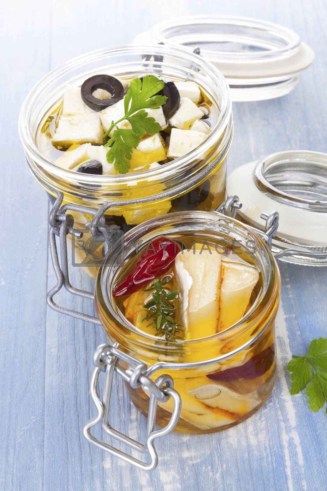 Marinated cheese in glass jar on blue wooden background. Culinary cheese eating.